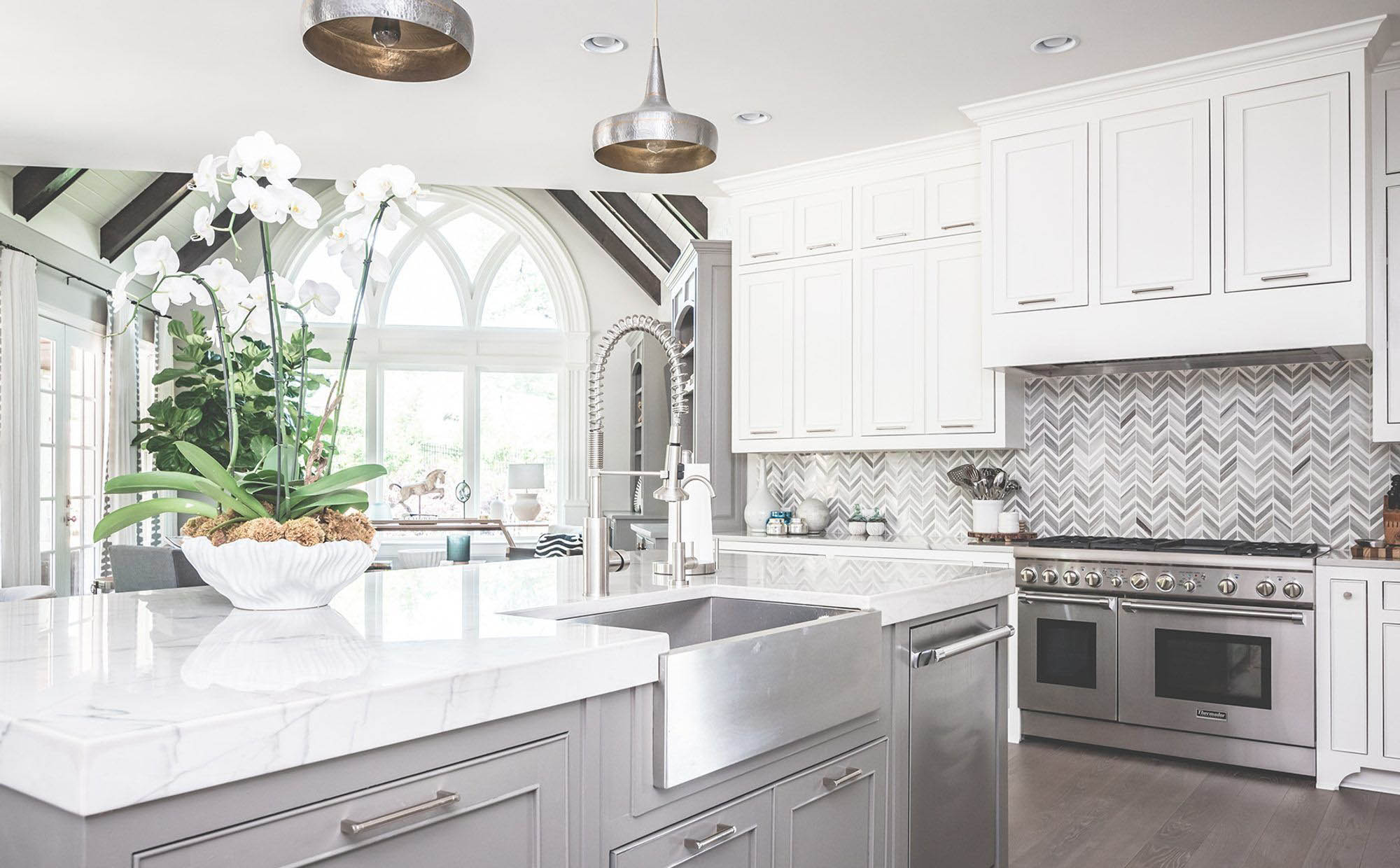 Single basin stainless steel farmhouse kitchen sink with stainless faucet. Gray cabinetry with stainless hardware and marble quartz countertops.