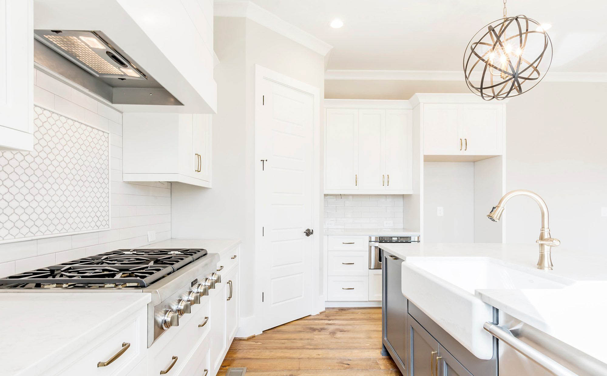 beautiful white kitchen with white countertops and white farmhouse sink with gray island cabinets