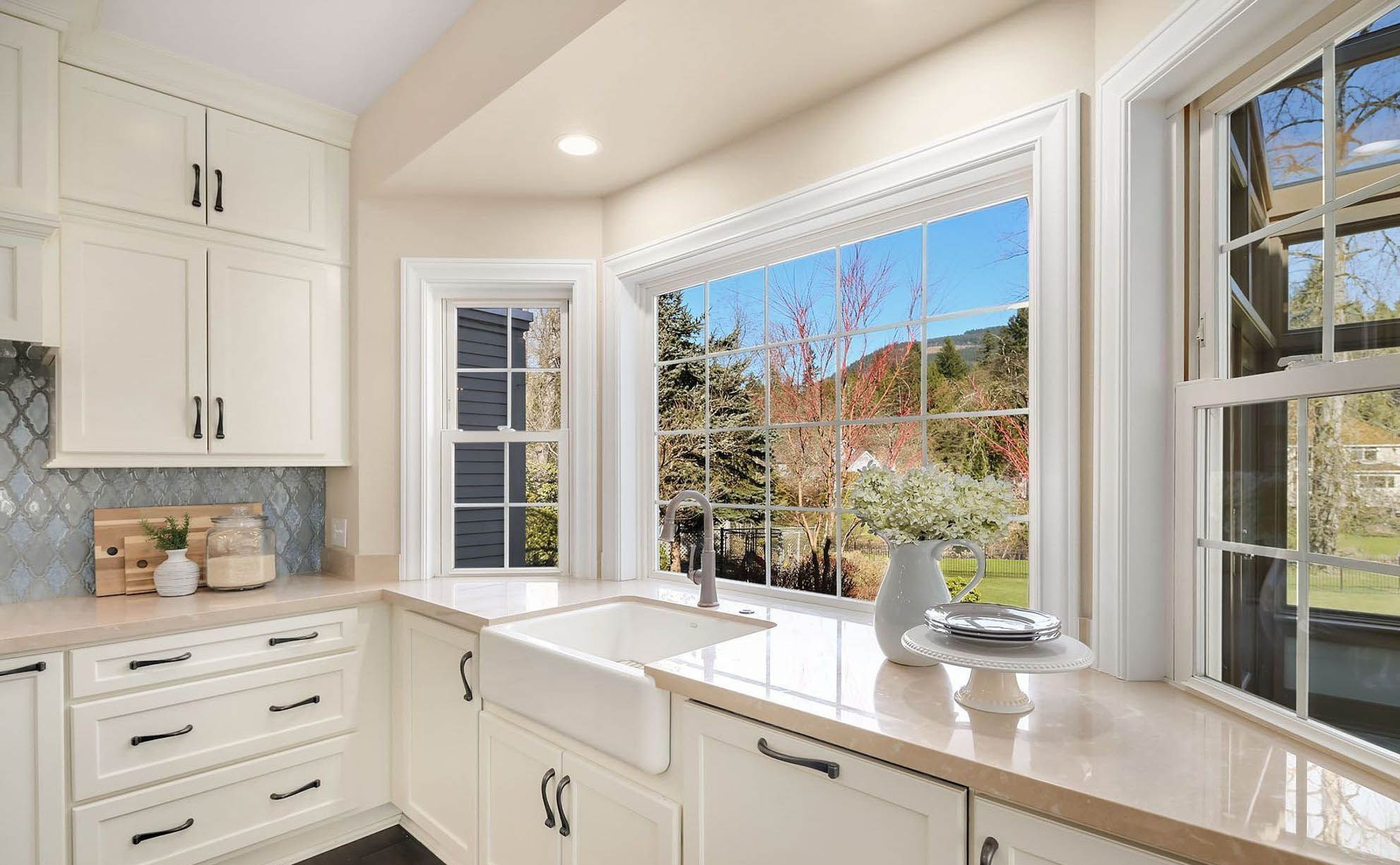 country style kitchen with a white enamel farmhouse sink with exposed apron and huge window