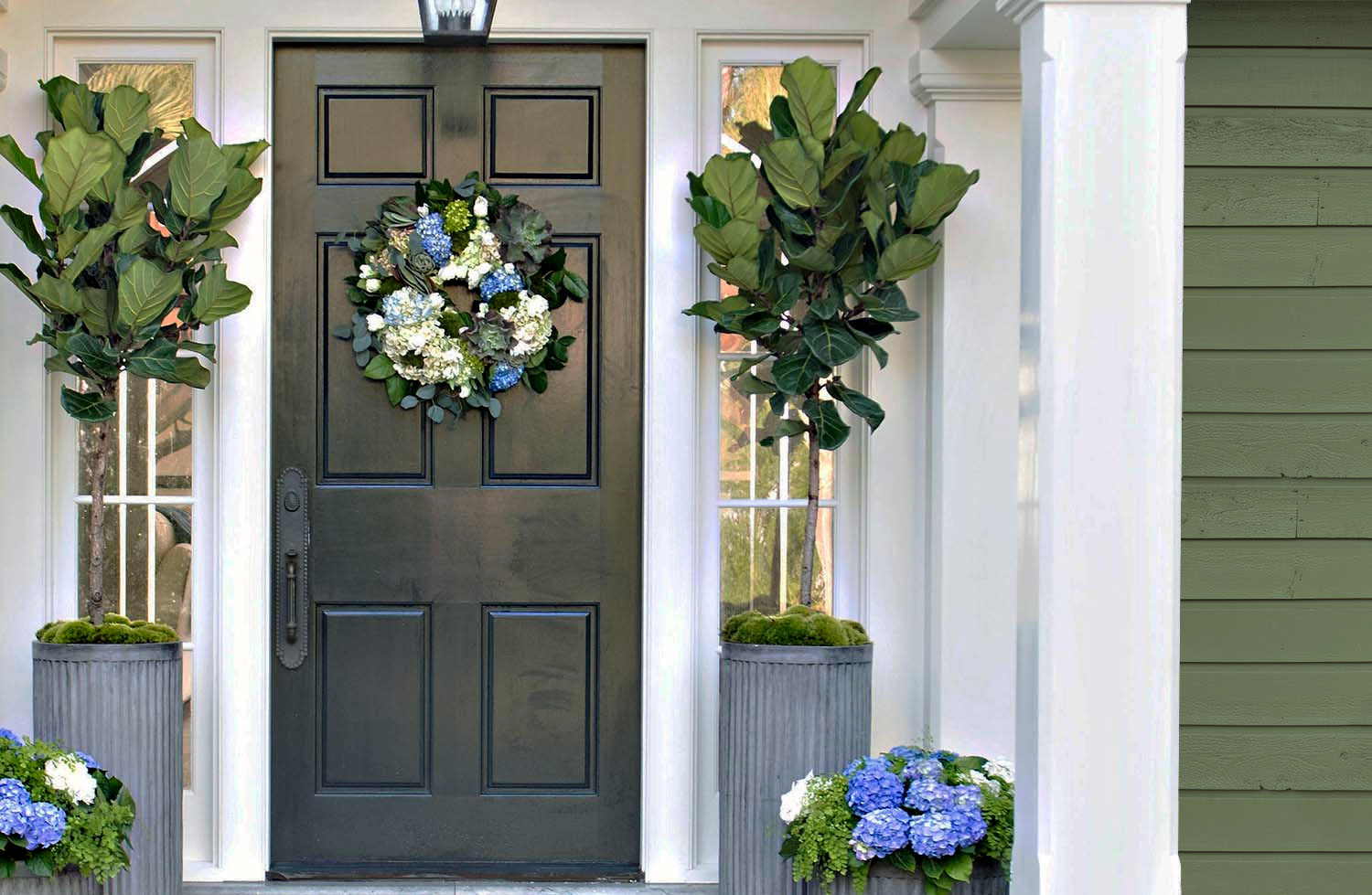 Beautiful home with green gray wood lap siding, a black front door and lots of porch flowers.