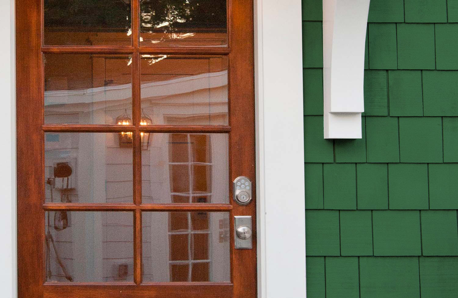 Green cedar shake siding with white trim and a real wood front door.