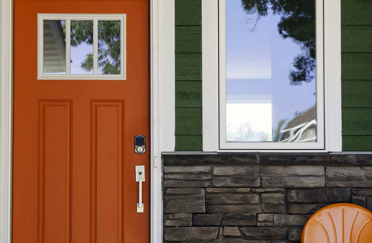 Dark Green house with a bright reddish orange front door and real stone veneer.