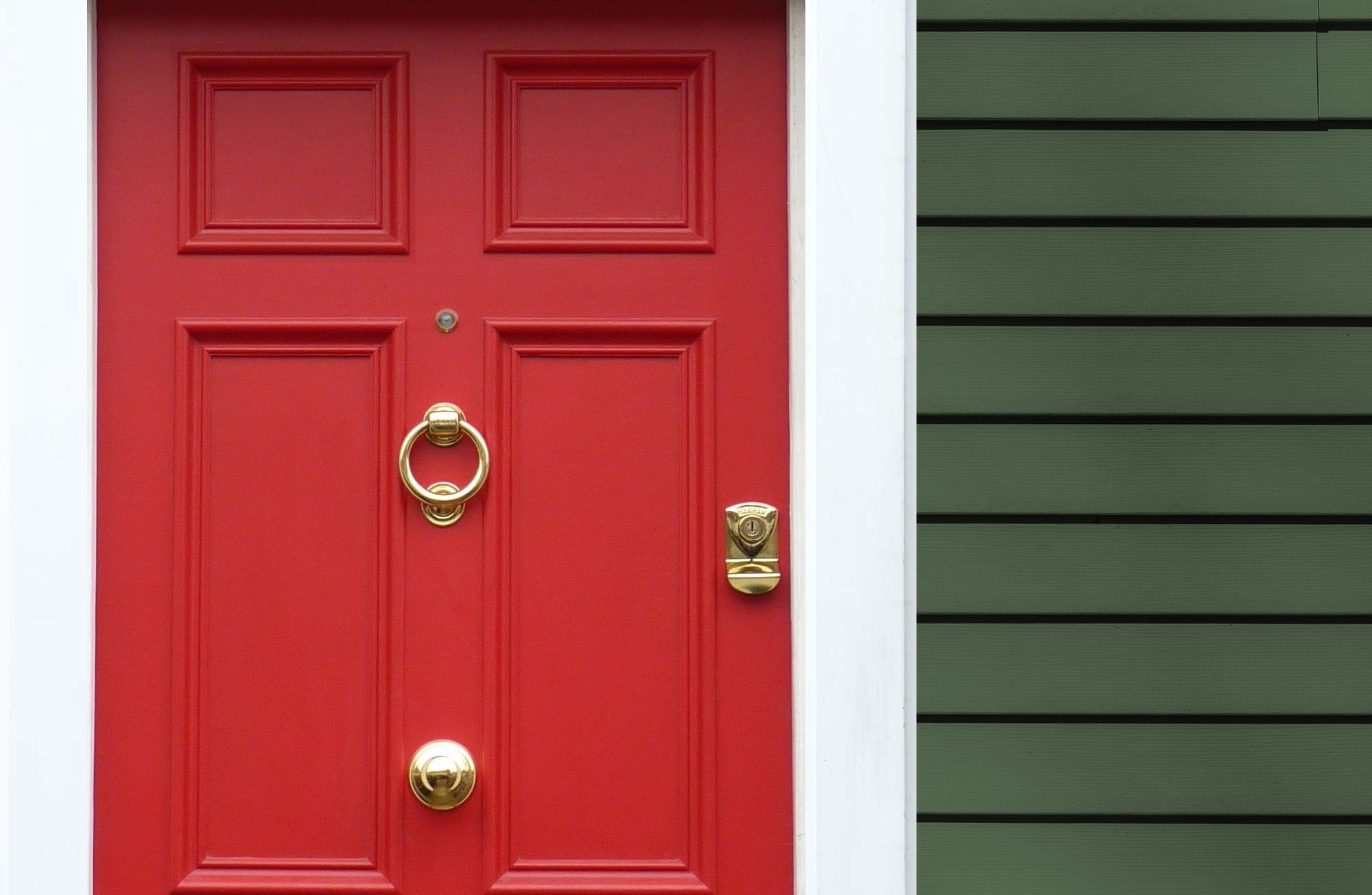 Forest green cedar shake siding with white trim and a bright red front door with gold hardware.