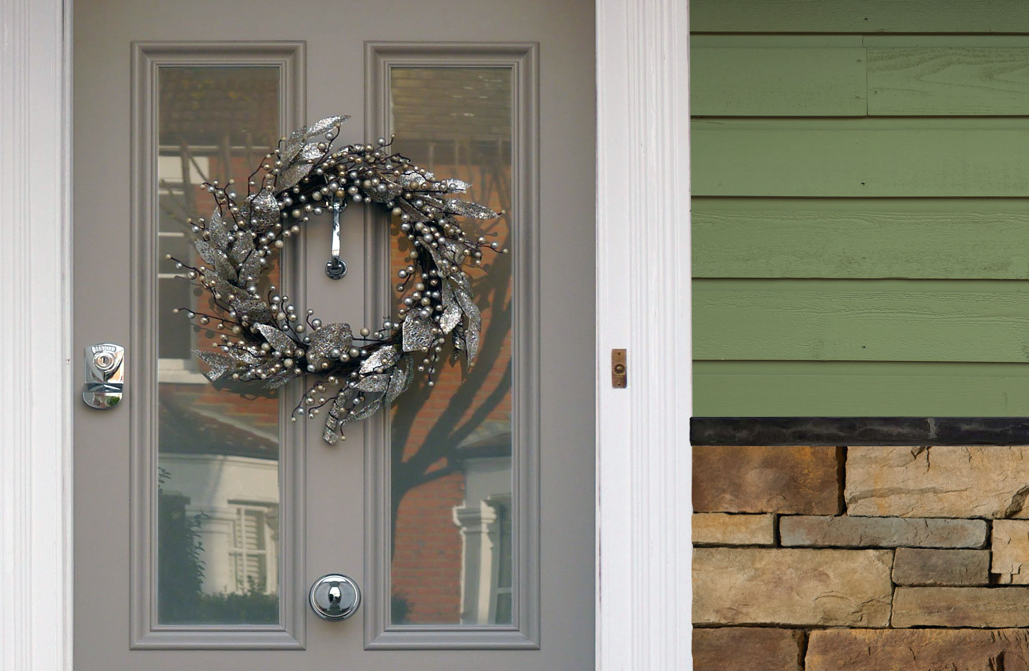 Green house with earth colored stone and a light gray front door with decorative silver wreath.