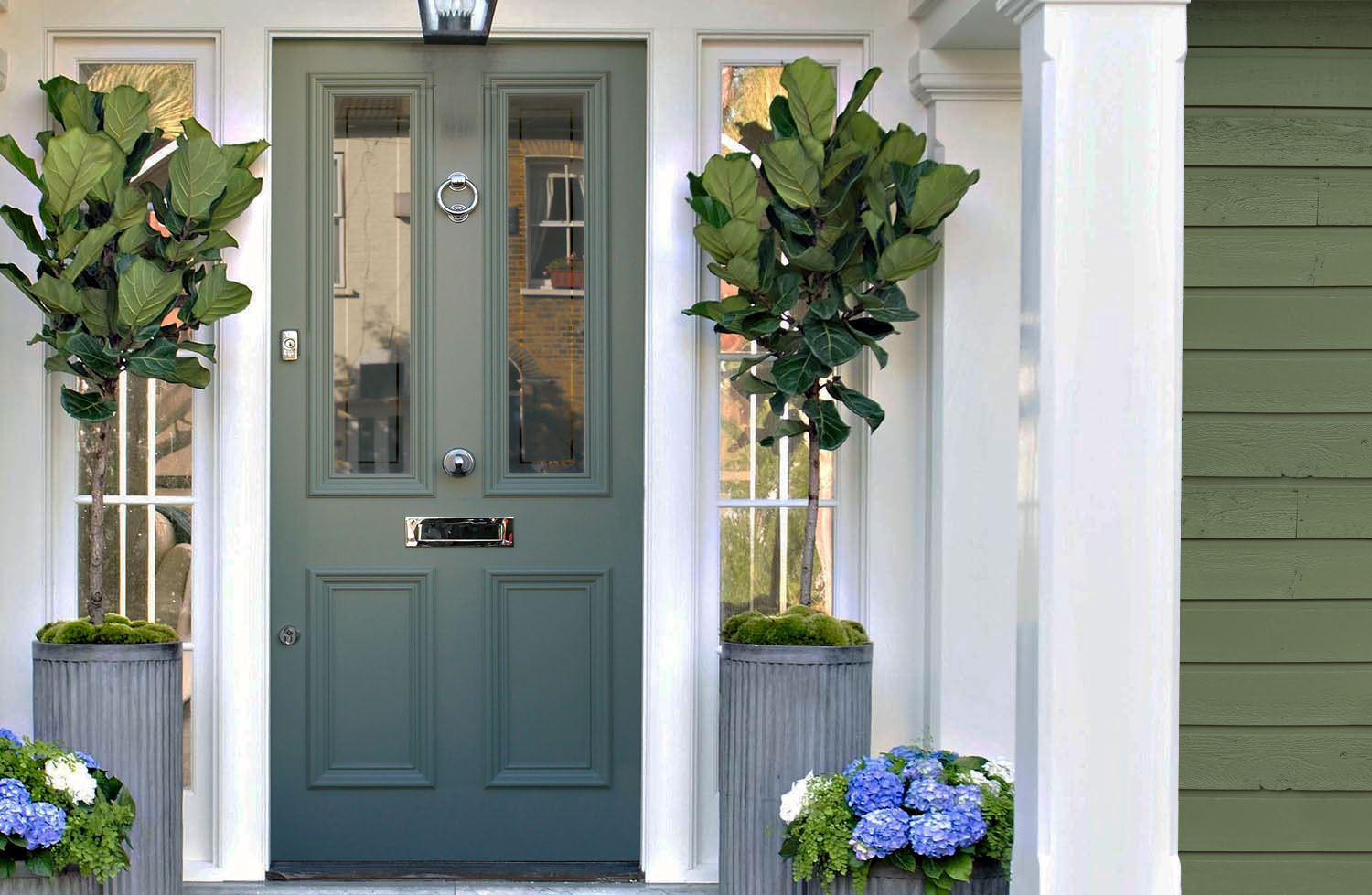 Green home with a teal front door, white trim and lots of porch plants.