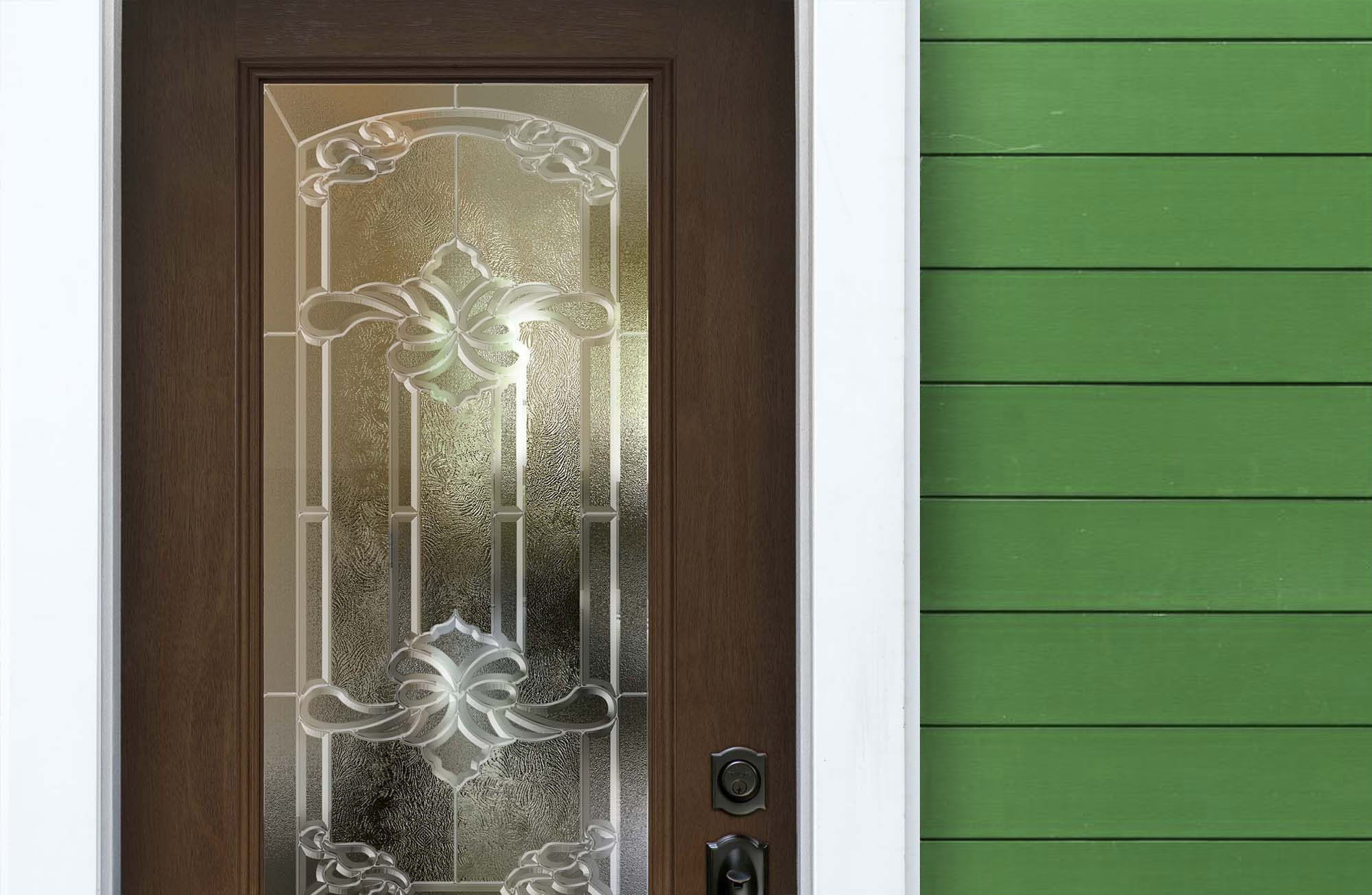 Green fiber cement siding with a cool brown real wood front door, stained glass and black door hardware.