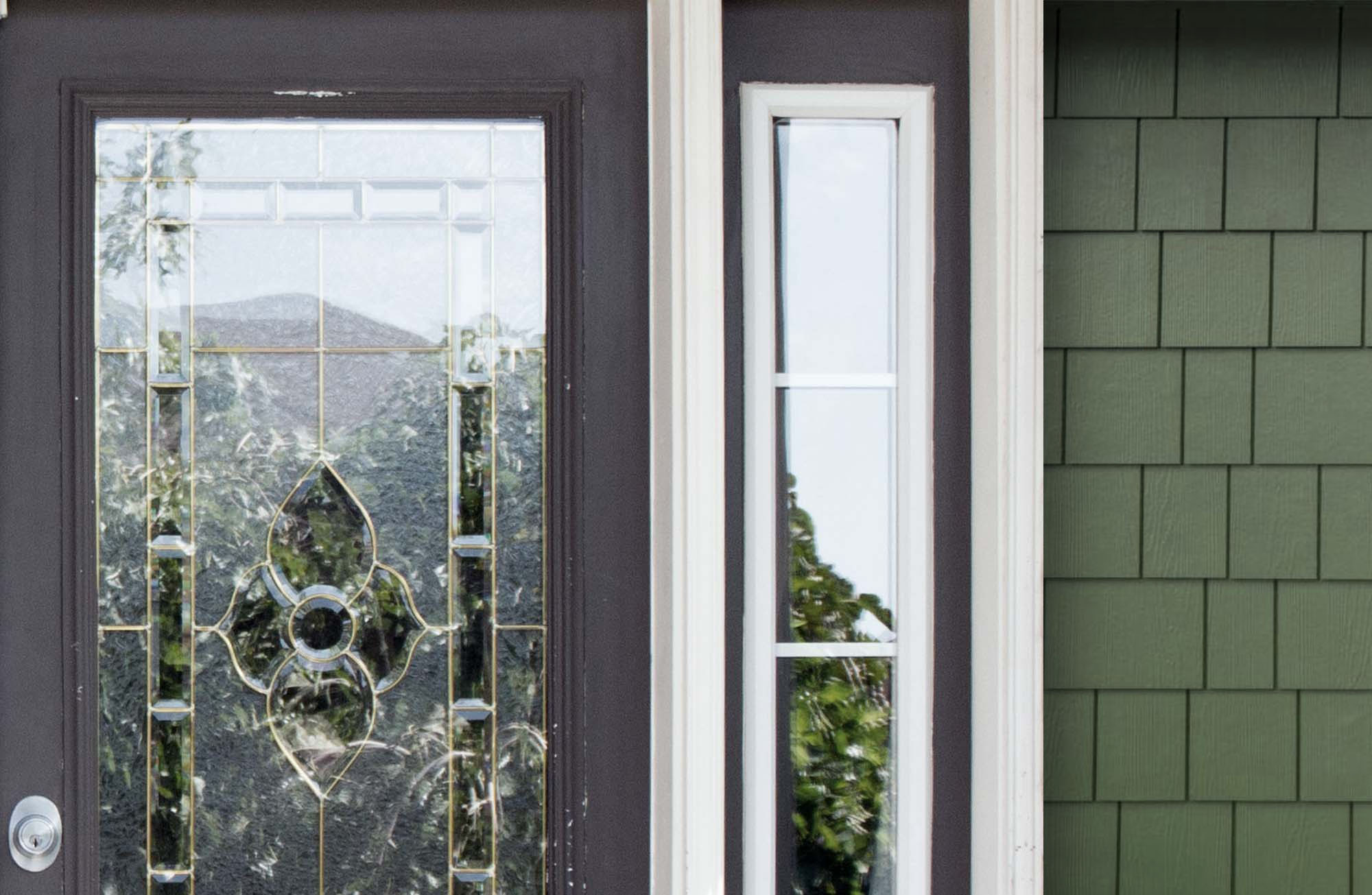 Green home with cedar shake siding and a dark gray front door.