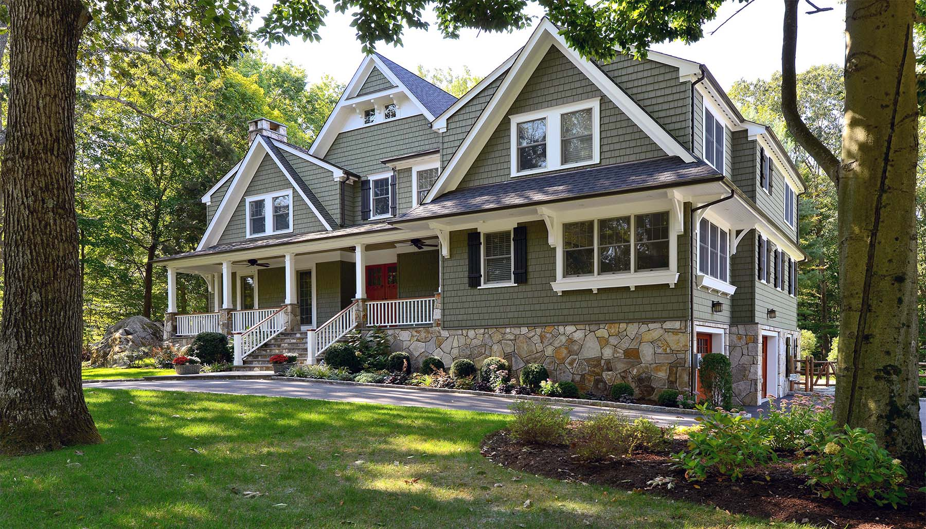 Fantastic custom home featuring green cedar shake siding with a red front door and lots of white trim.