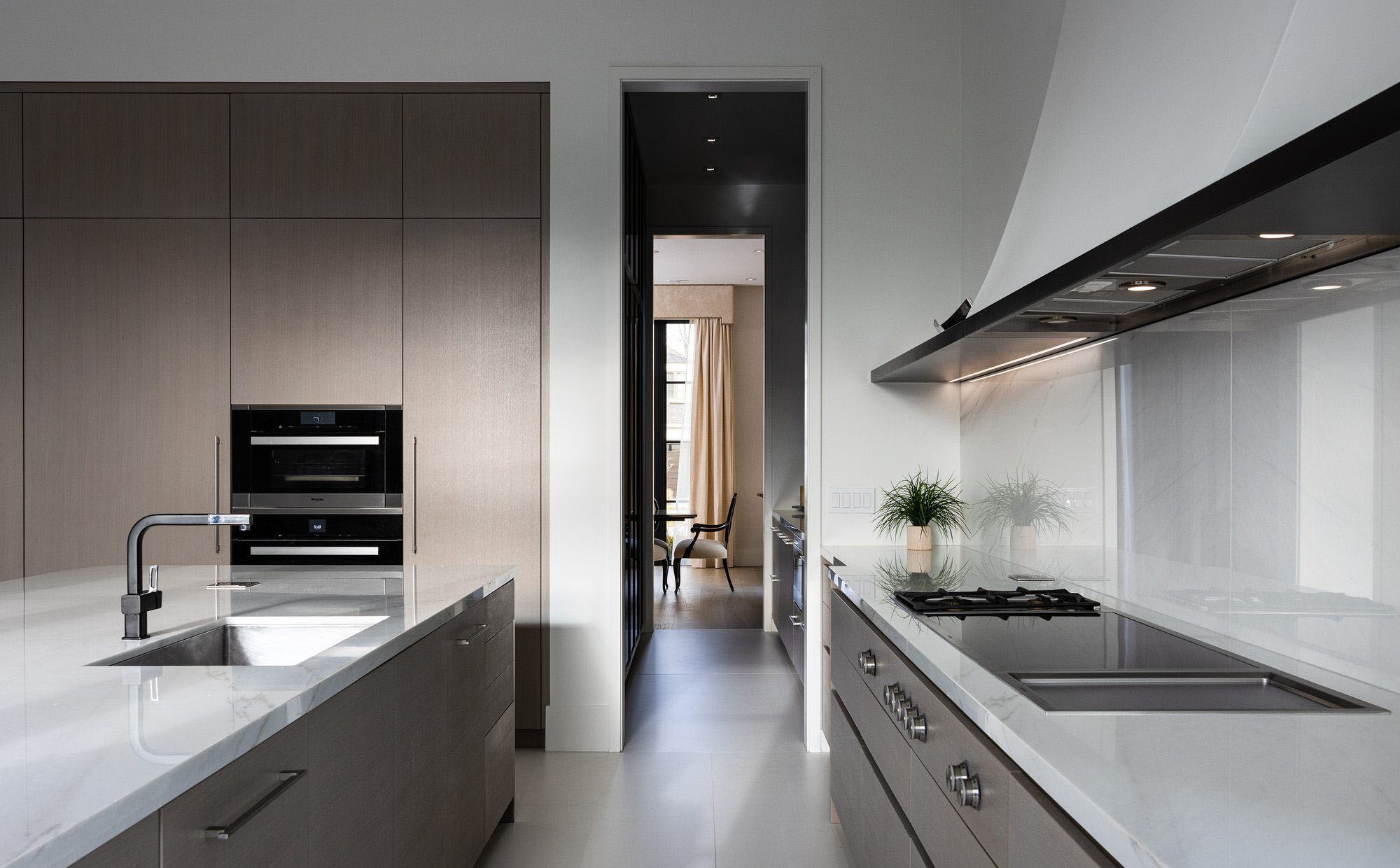 Beautiful modern kitchen design with a muted color palette. Light grayish wood cabinets with marble quartz countertops and backsplash.