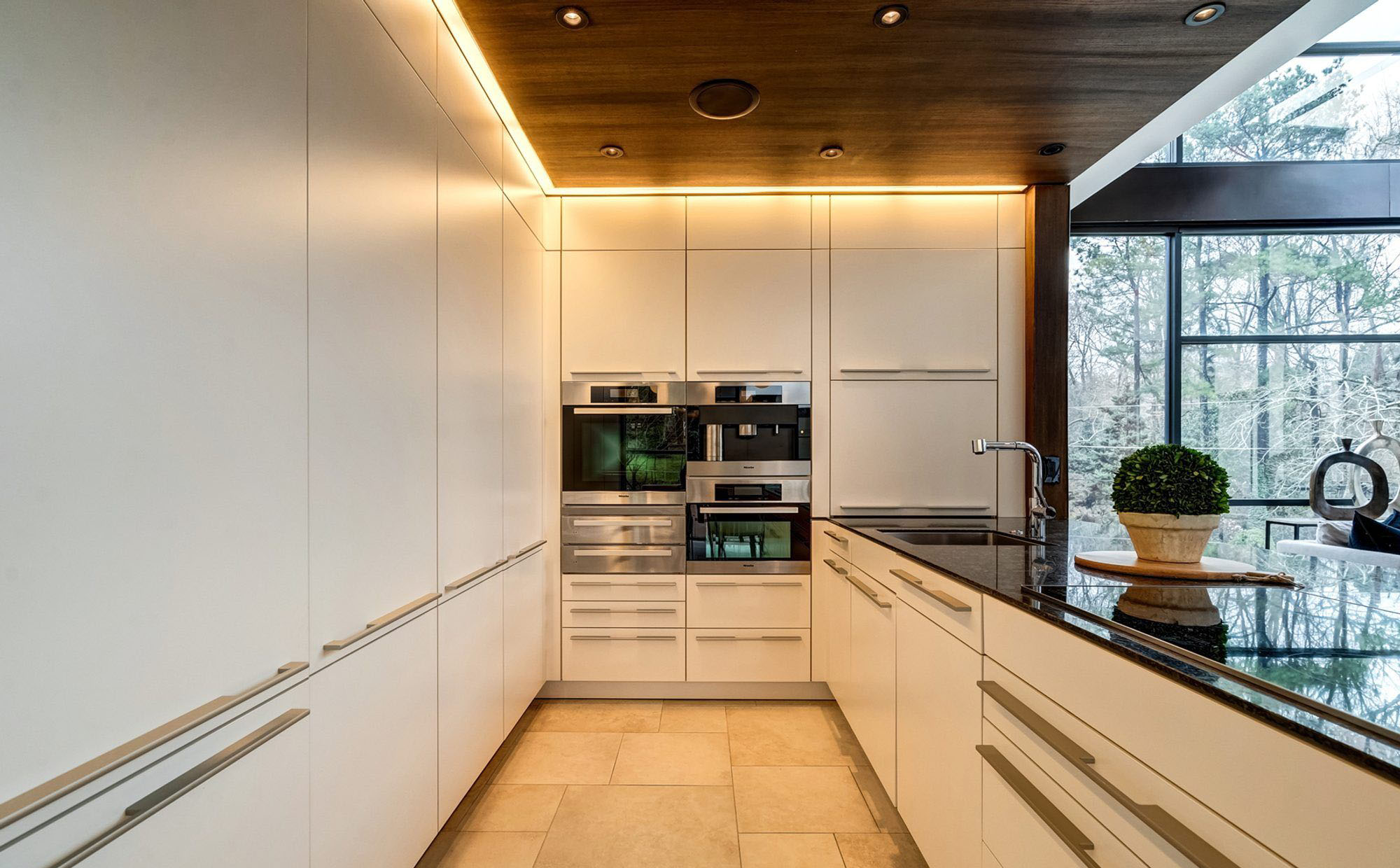 Hidden recessed LED strip lighting in a modern kitchen with cream colored flat faced cabinets.