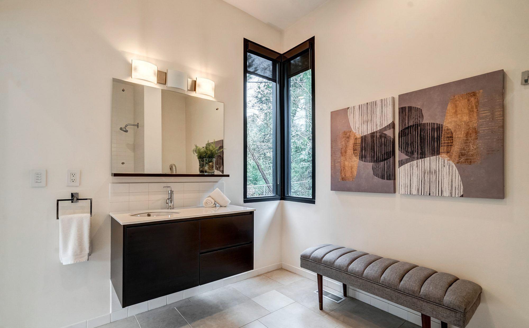 Modern bathroom with a tall and thin corner window.