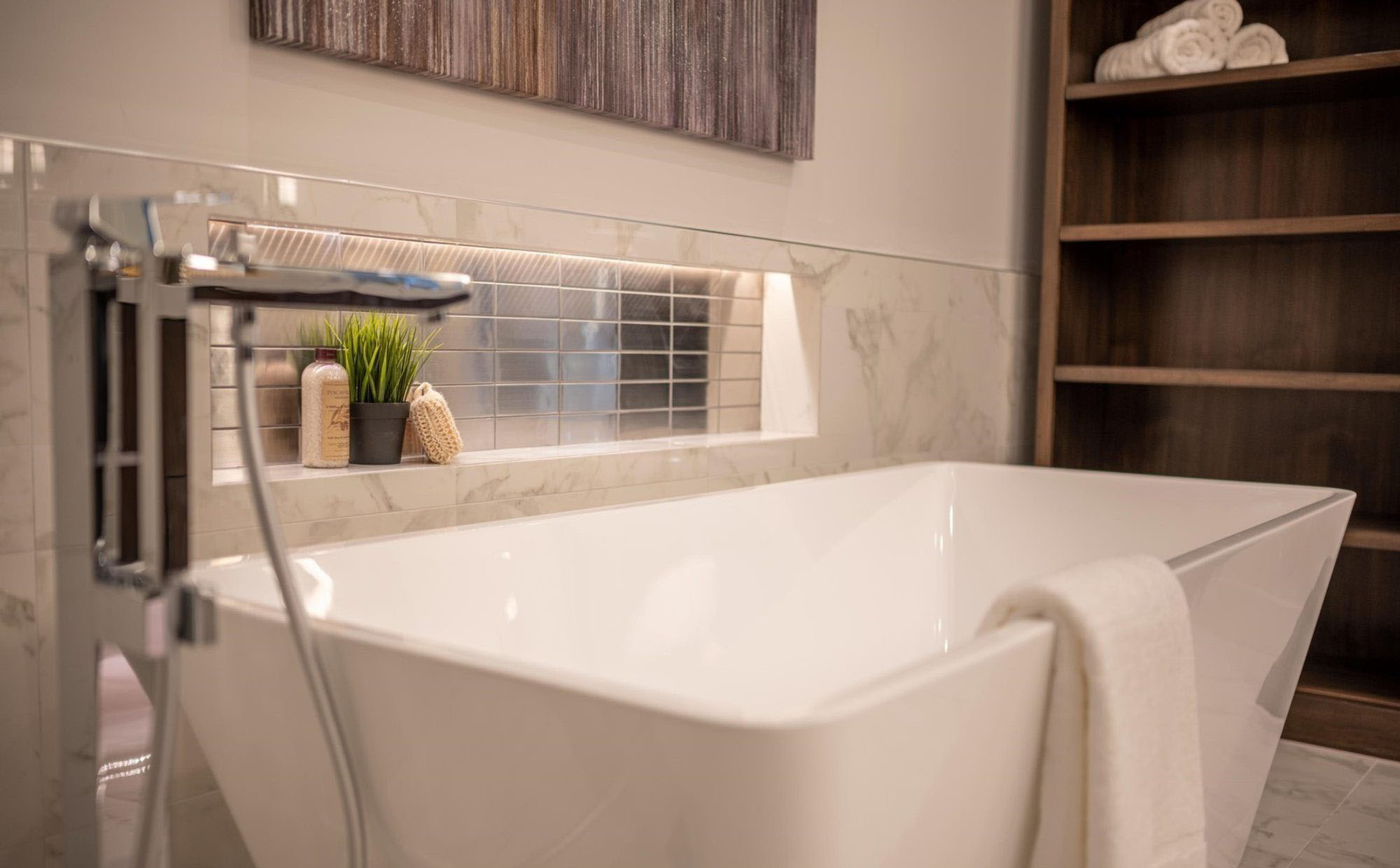 Modern bathroom with large white soaking tub, chrome faucets and built in shelf with metallic tile.