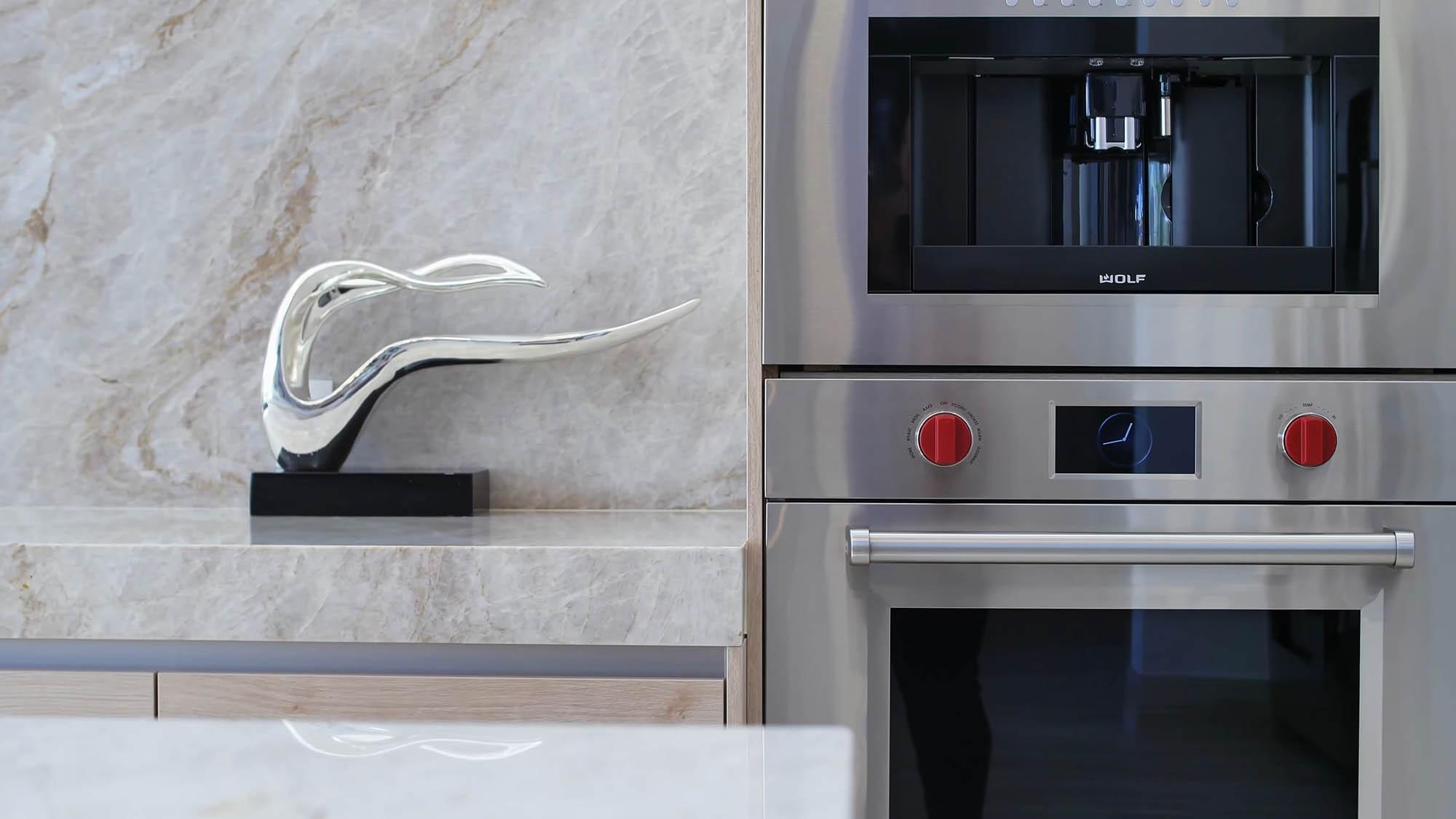 Modern luxury kitchen with solid stone slab backsplash. modern home design details.