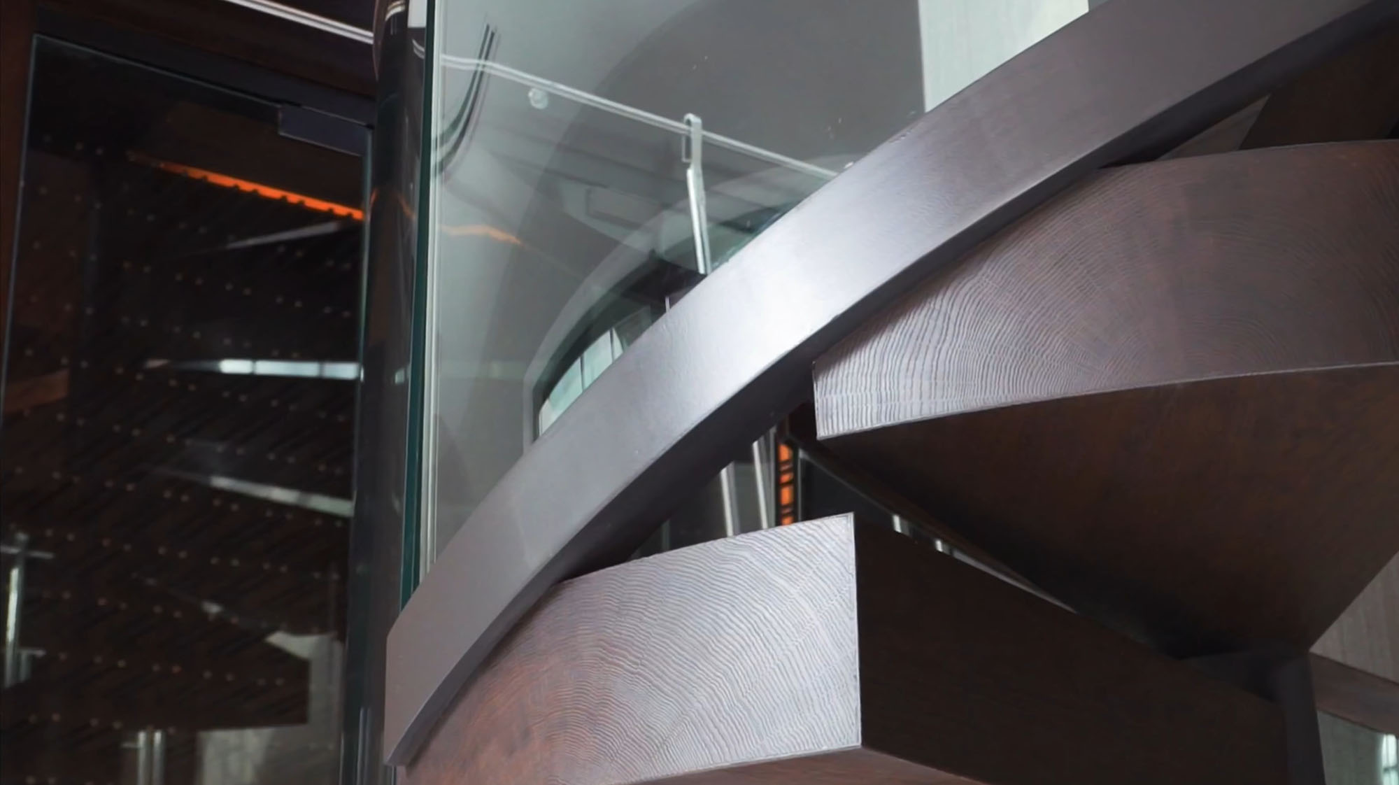 Closeup view of a modern metal and wood staircase made out of solid wood slabs.
