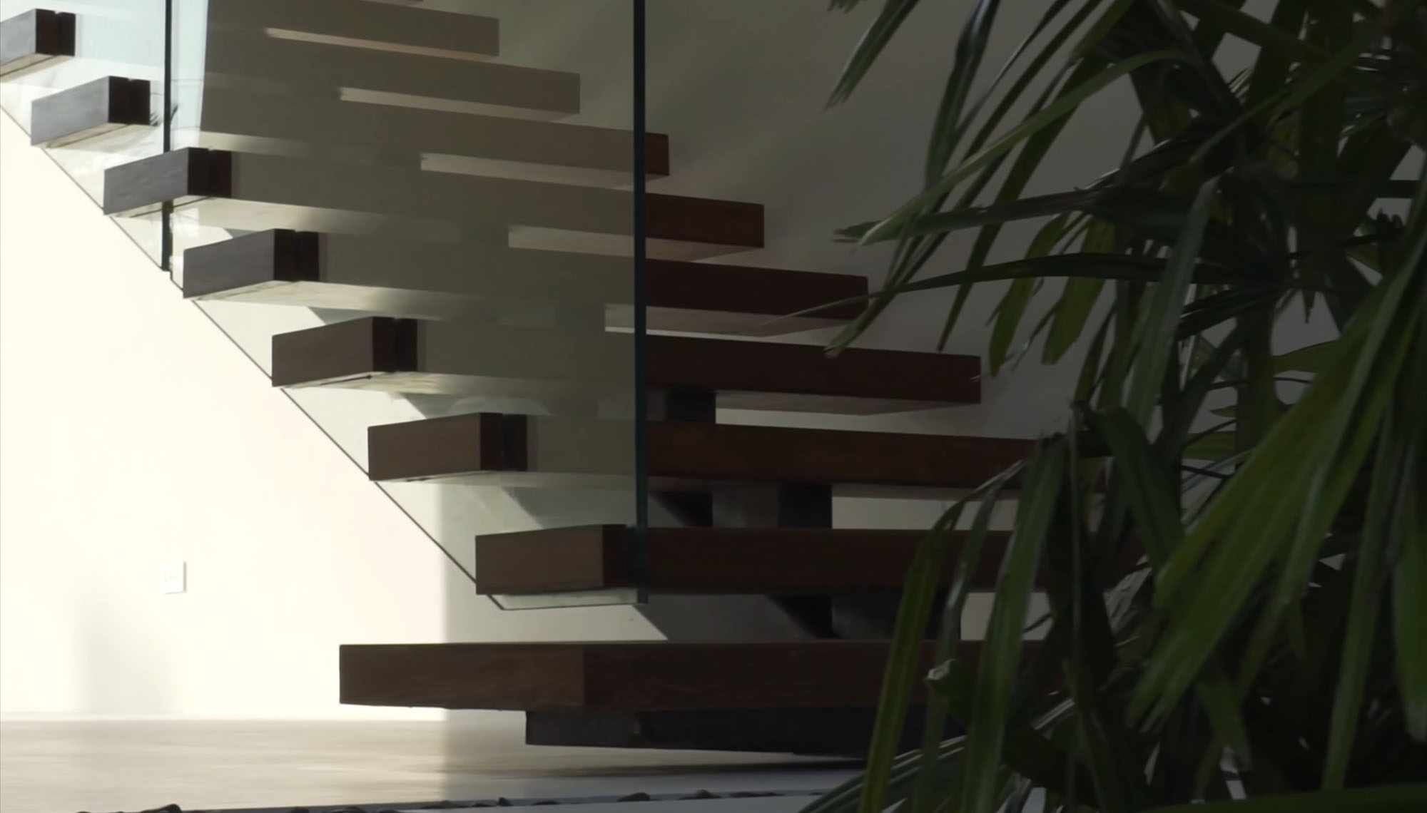 Beautiful modern staircase with open riser wood steps, glass railing and a steel frame.