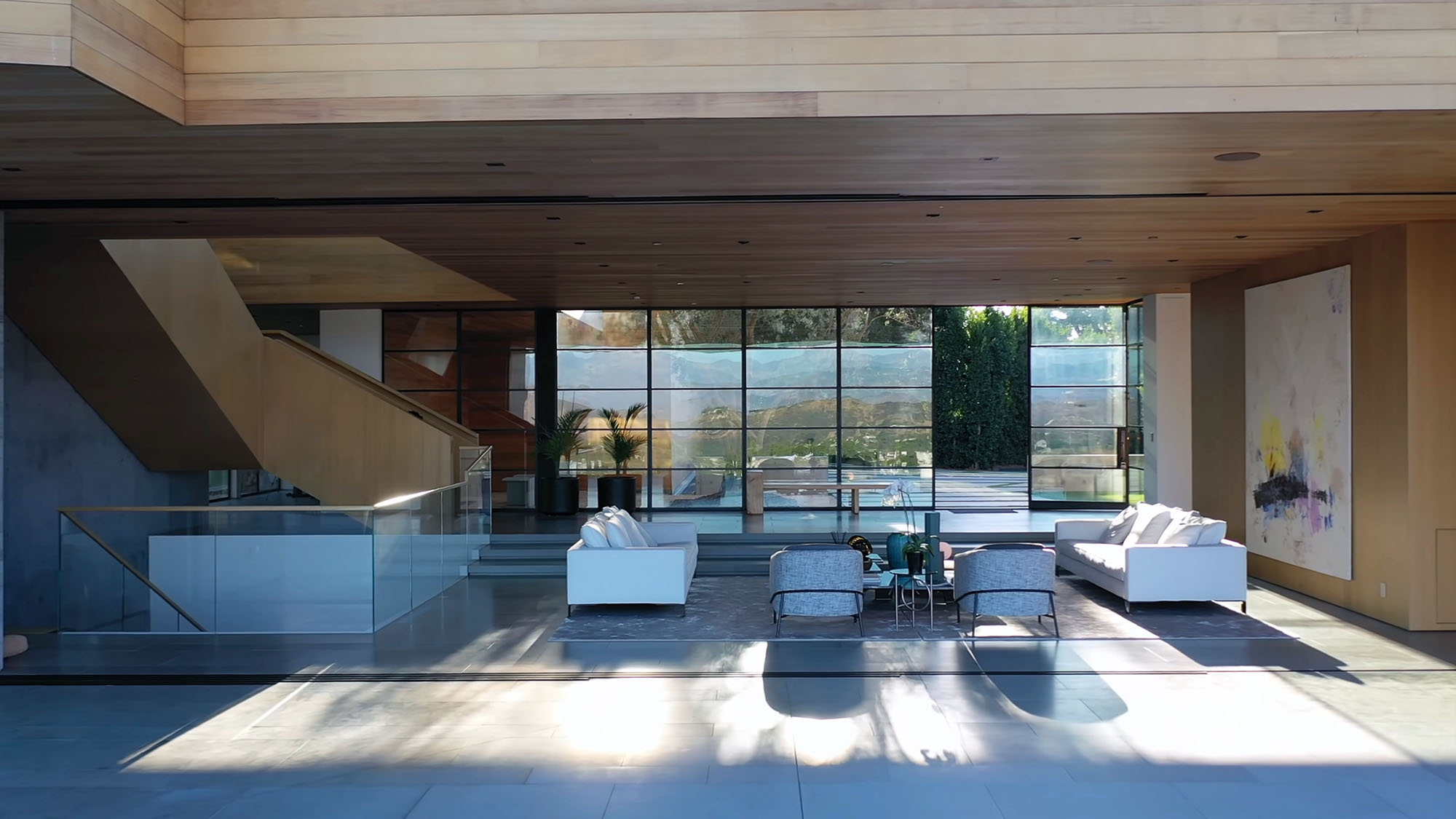 Modern living room design with walls of glass that recess to expose indoor outdoor living.