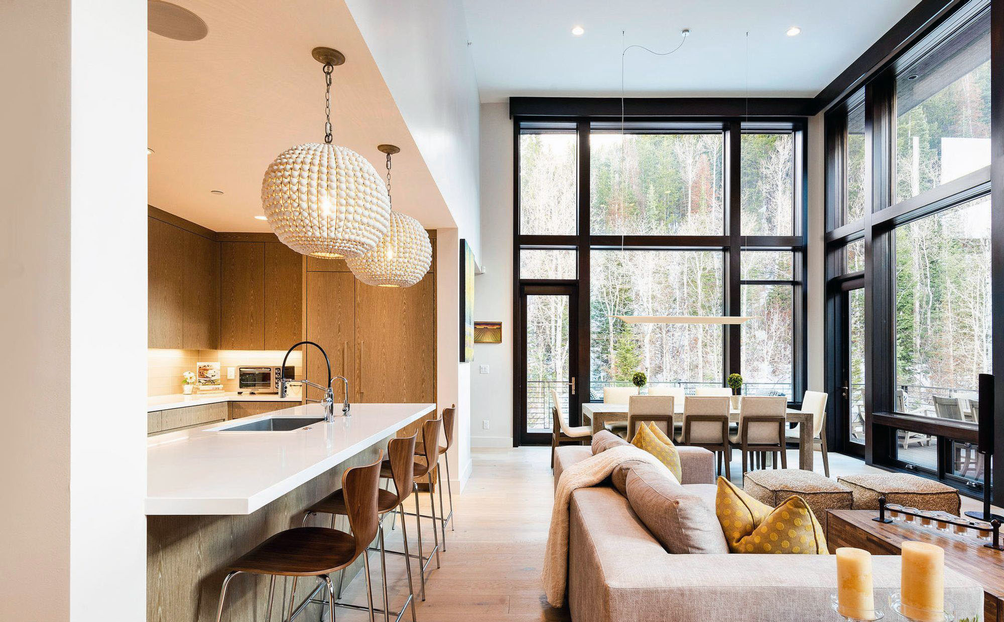 Open floor plan modern home with a beautiful kitchen design. Walls of glass 2 stories tall.