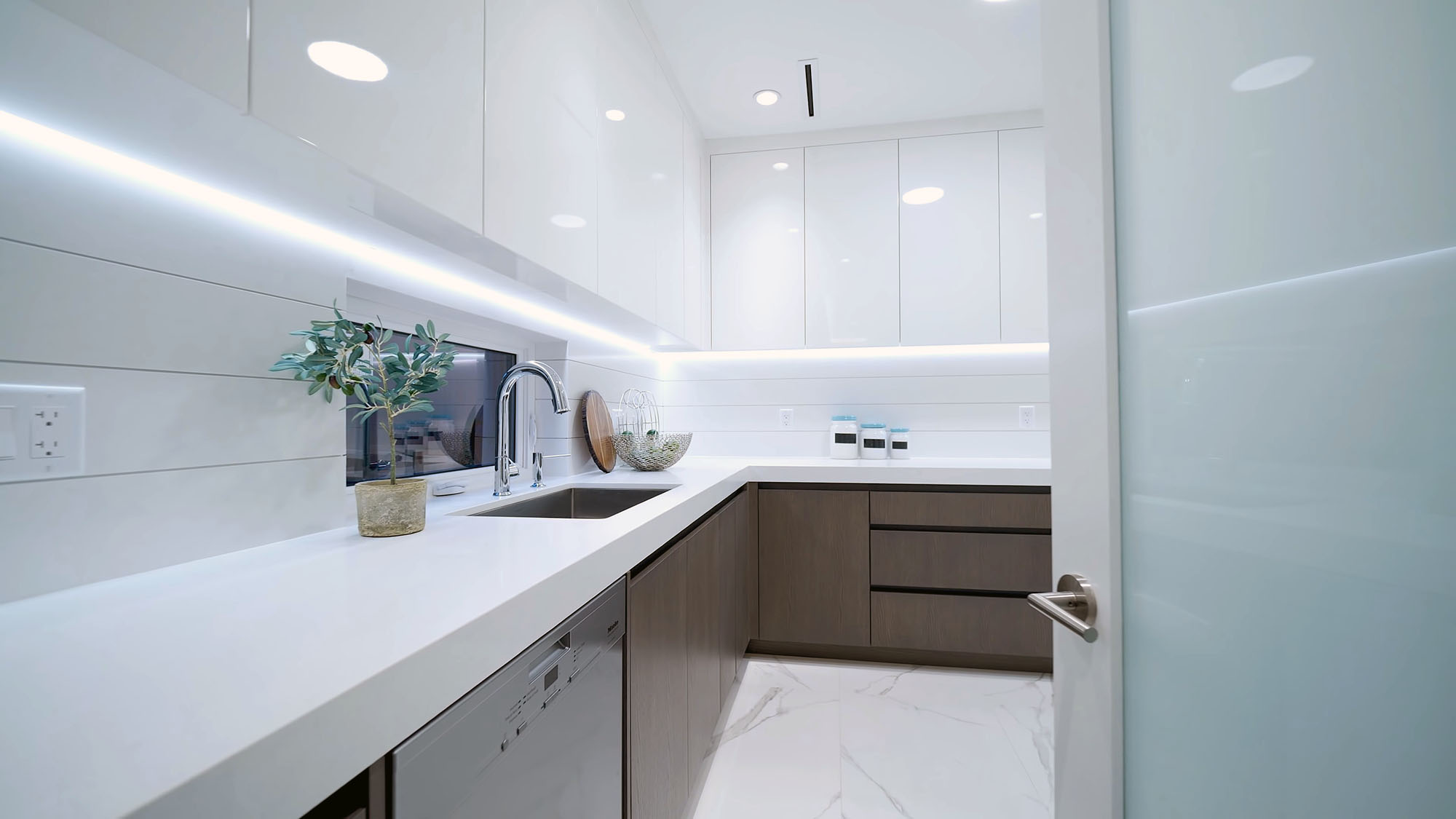 Ultra modern prep kitchen with white flat faced upper cabinetry and grayish wood base. White quartz countertops with a shiplap style backsplash.