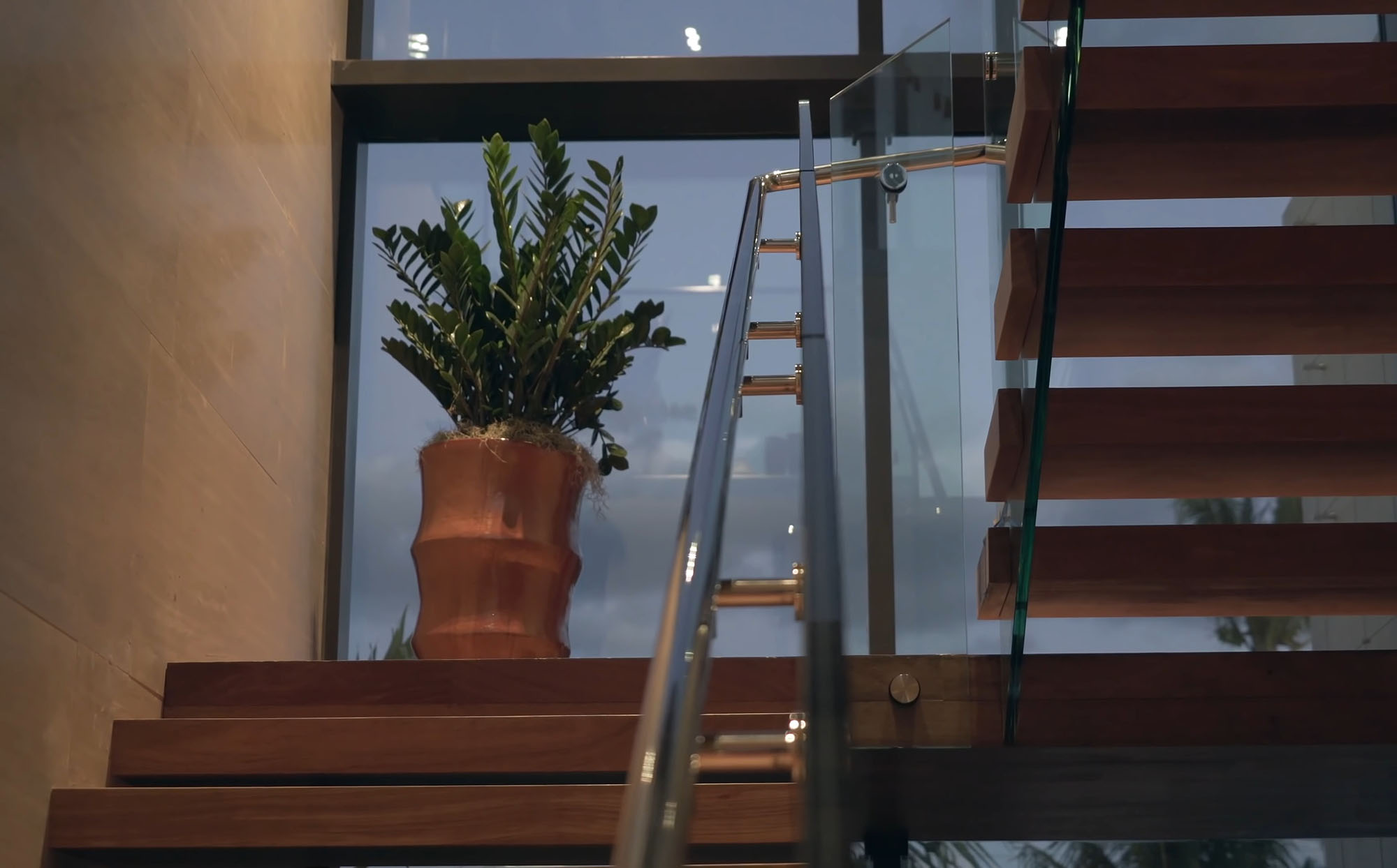Modern staircase with open riser wood steps and glass railings.