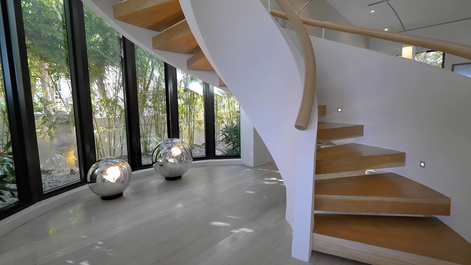 Modern white and light wood curved staircase design with open risers.