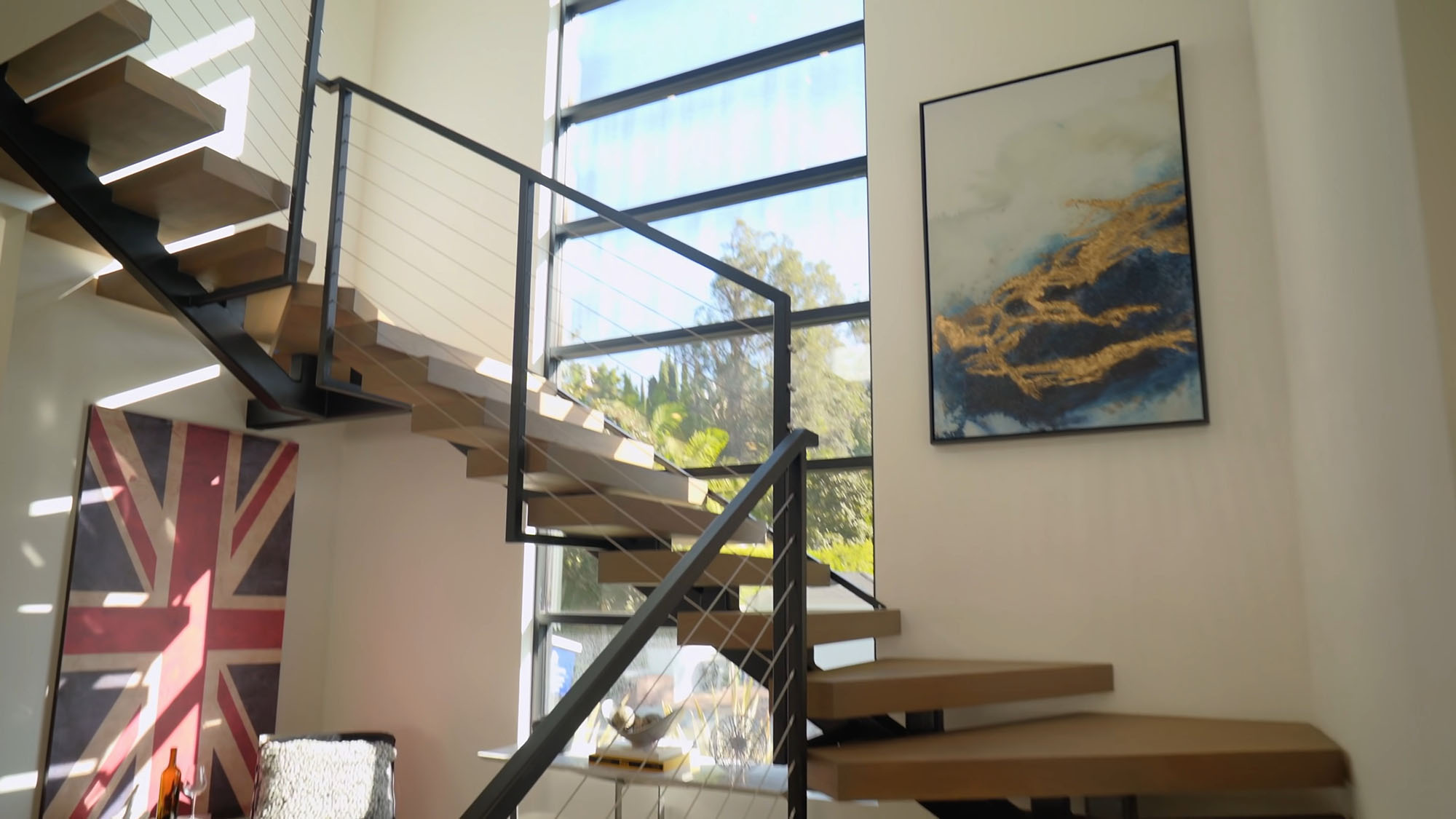 Modern metal and light wood staircase with metal and wire railings in front of a huge window.