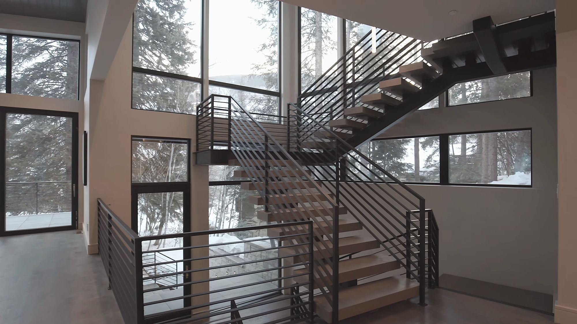 Windowing metal and wood modern staircase in front of a wall of glass.