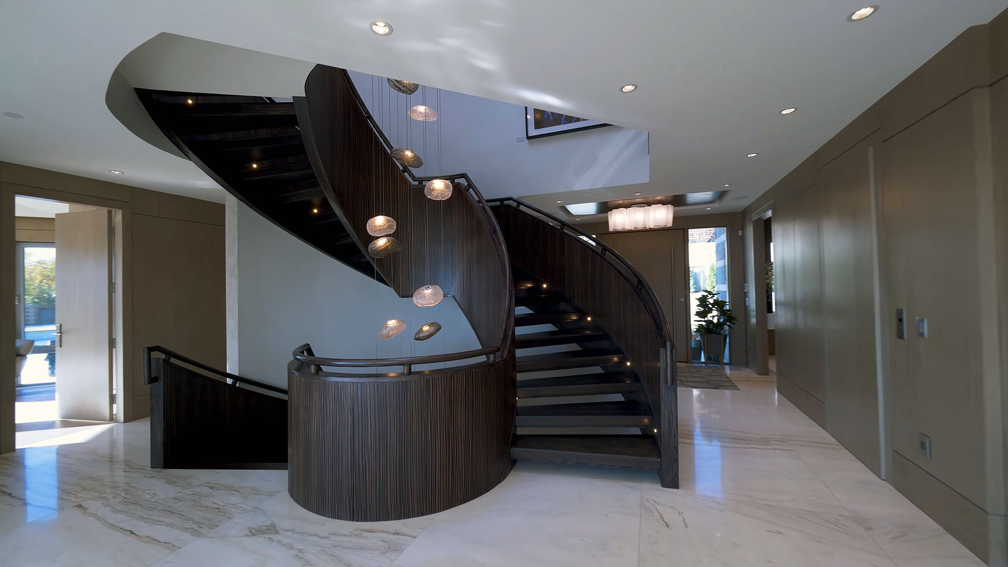 Curved ultra modern dark brown staircase made from wood and steel.