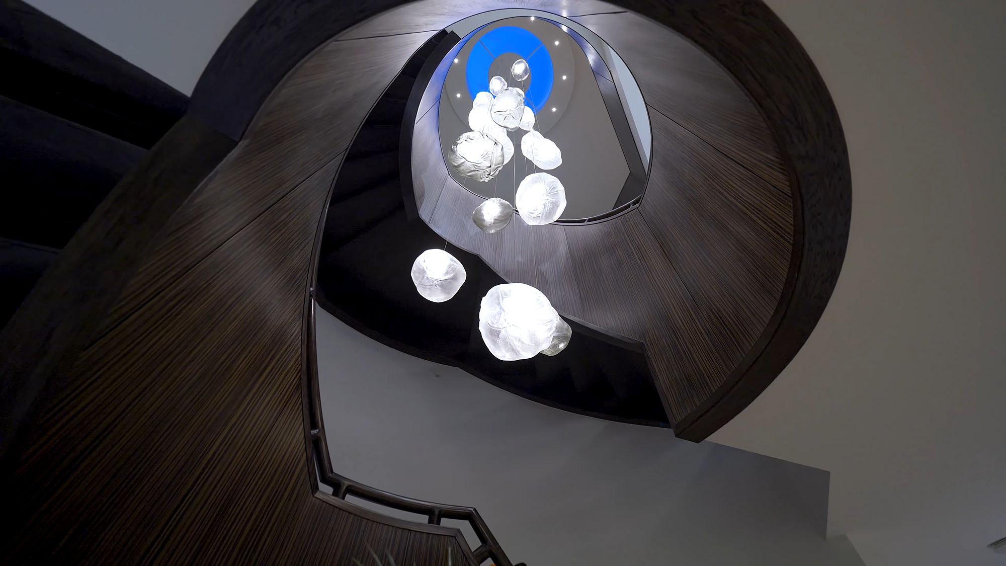 Grounds eye view of a curved modern staircase with chandelier and dome skylight.