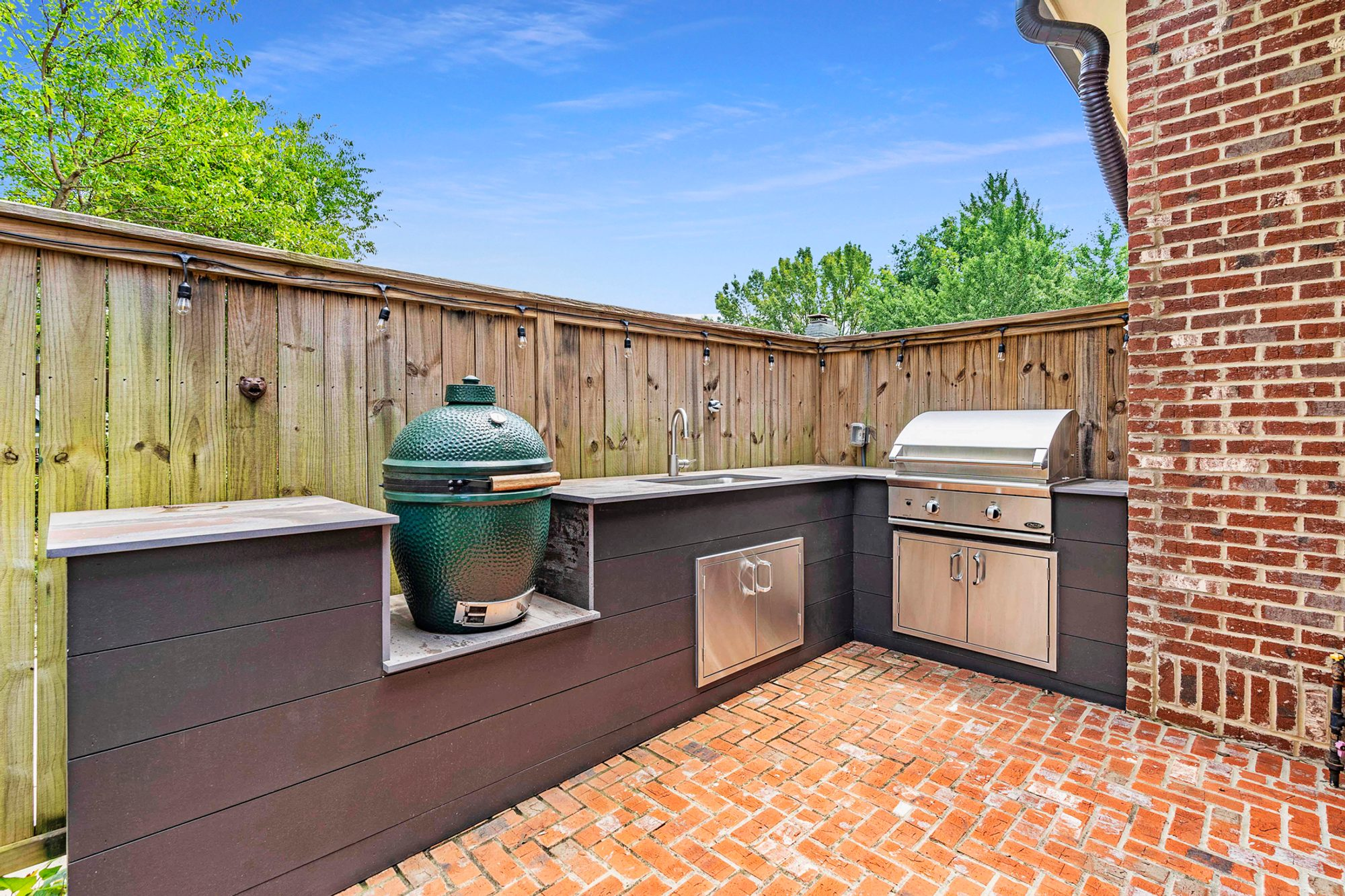 Red brick herringbone patio design with an outdoor kitchen.