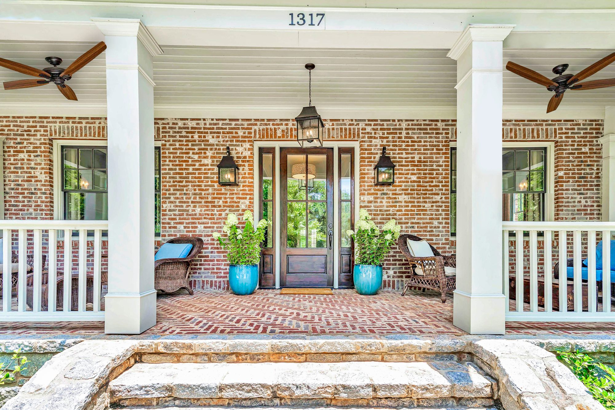 Covered red brick front patio with herringbone pattern and square columns, stone steps. Red brick home with a dark wood front door.