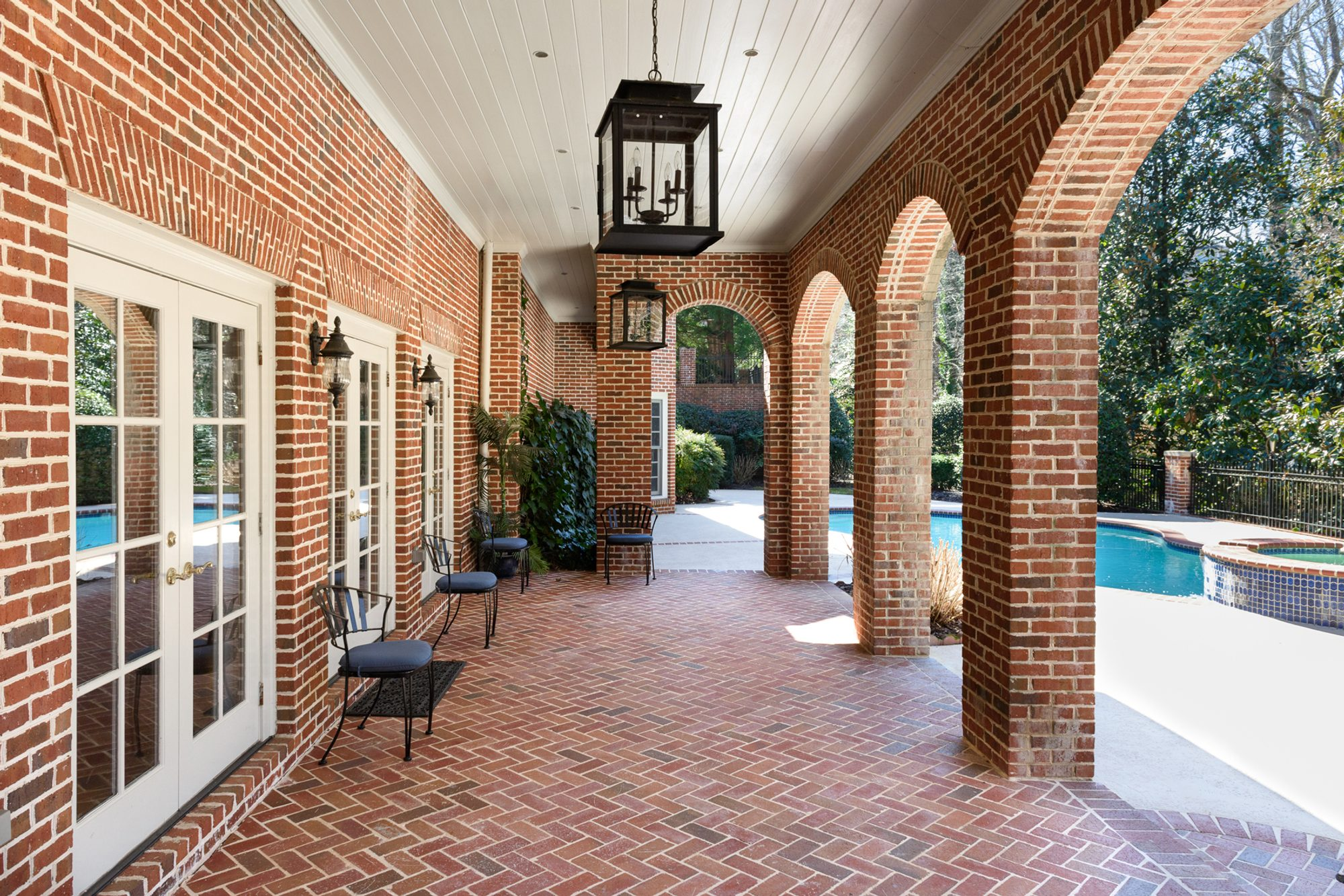 Covered herringbone red brick patio with border trim, red brick siding and columns.