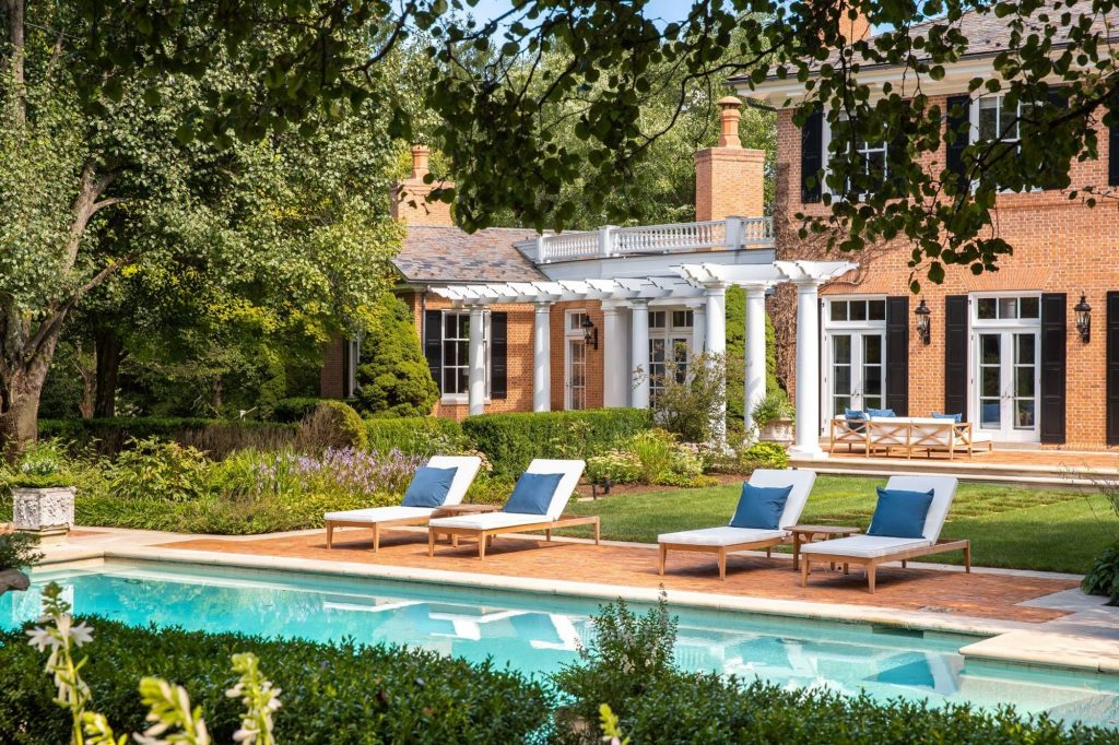 Poolside red brick patio with lounge chairs.
