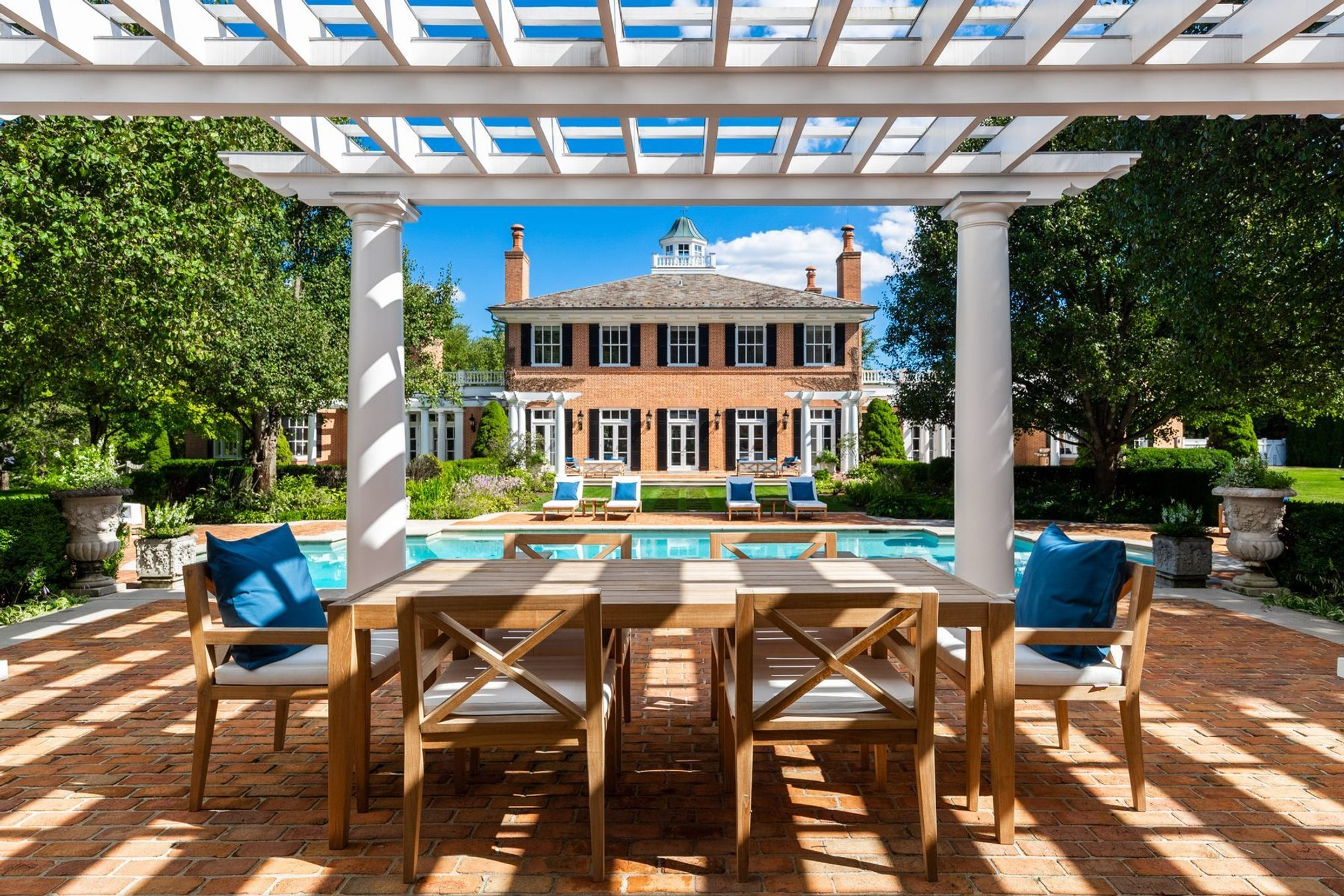Red brick subway style poolside patio with a custom built white arbor. Wood outdoor furniture with table and six chairs. White cushions with blue pillows.