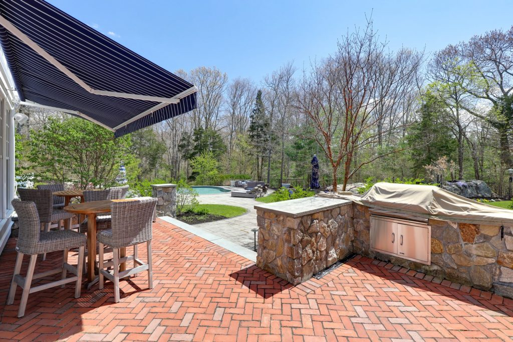 red brick herringbone pattern paver patio with border and real stone walls with built in grill