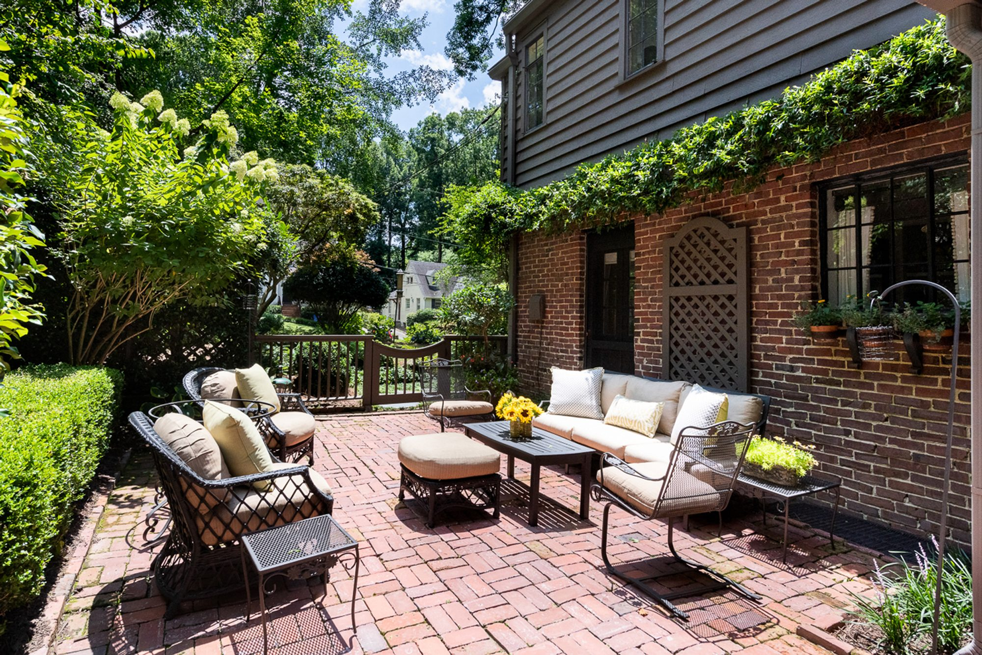 Red brick backyard patio with a basket weave pattern.  Black outdoor furniture set with cream colored cushions.