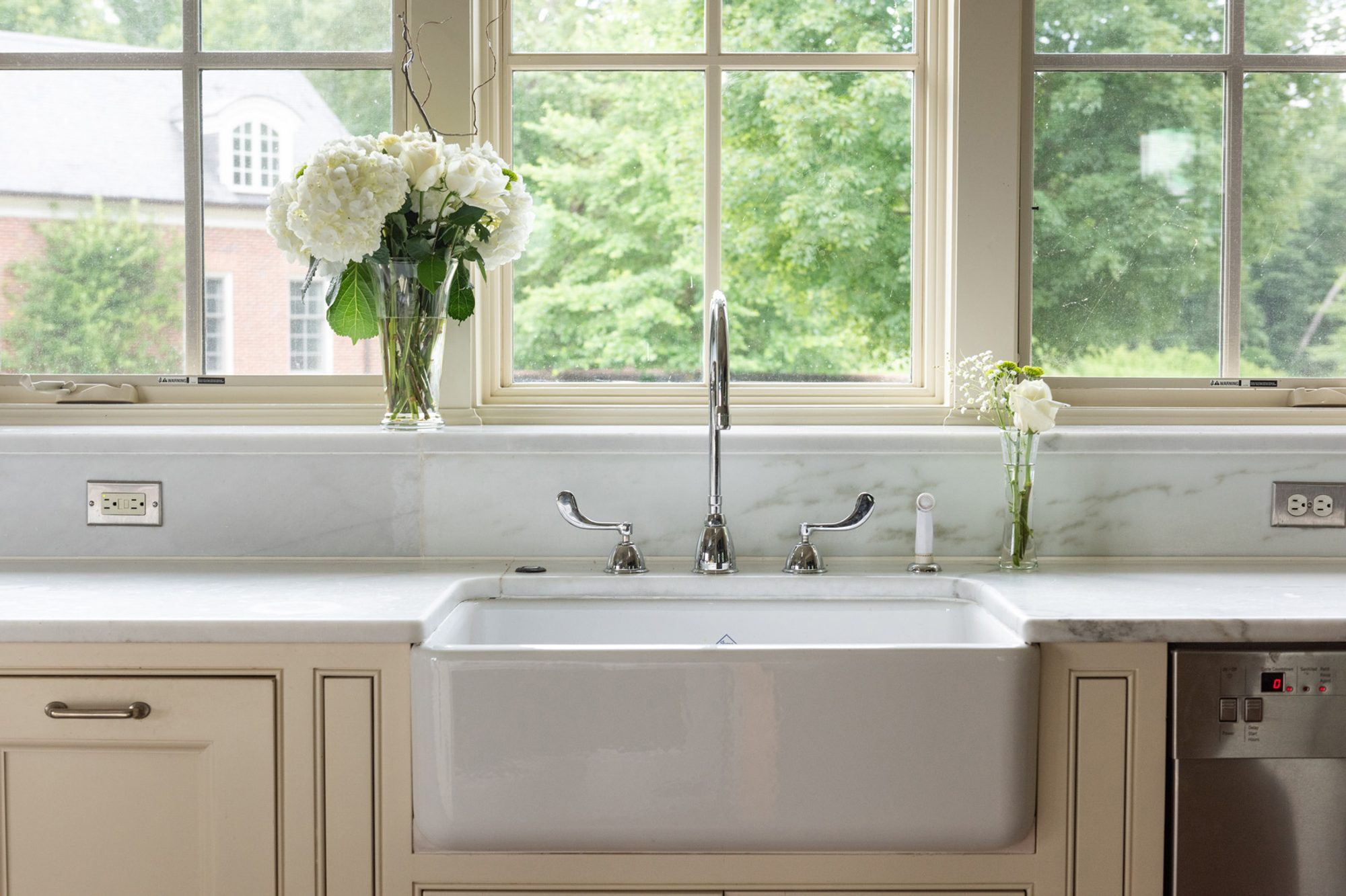 White cast iron farmhouse sink with cream cabinets and a marble backsplash. Chrome faucets and stainless steel appliances.