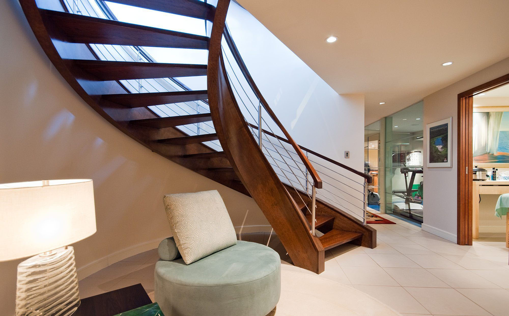 Beautiful modern staircase with a curved design. Open risers with metal horizontal balusters.