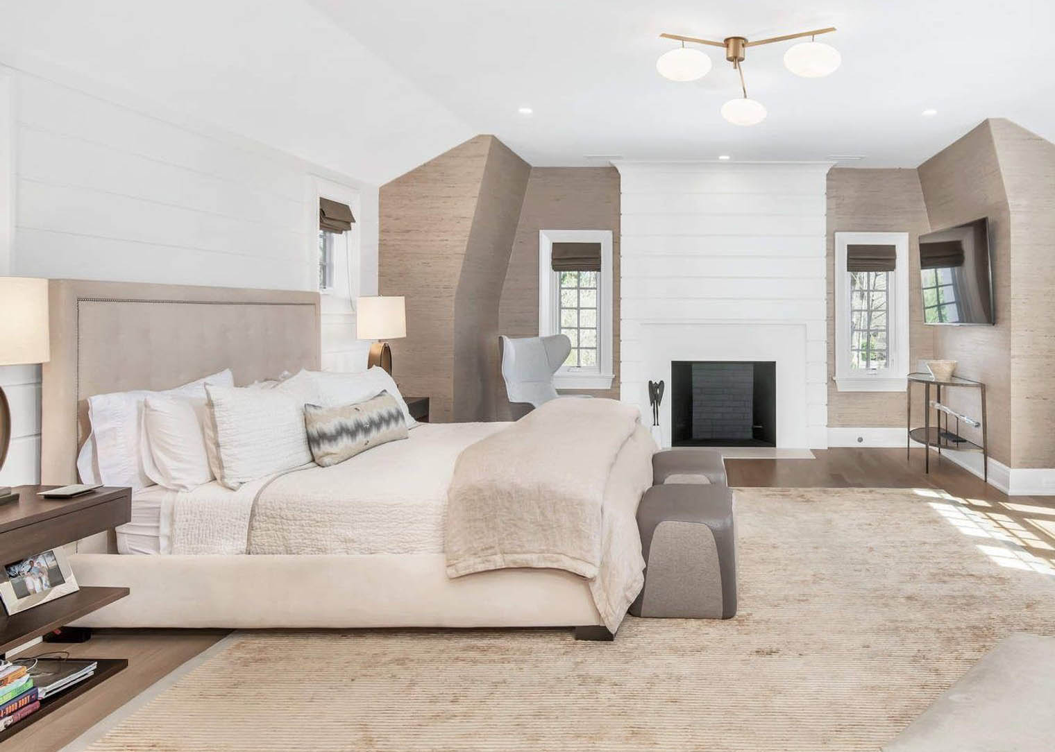 Master bedroom with horizontal shiplap wall paneling and wood burning fireplace.