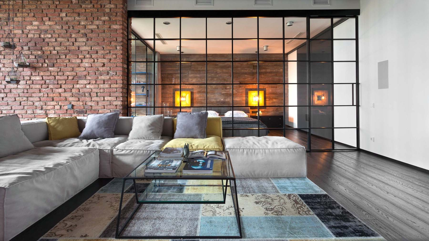 Red brick wall in a modern home featuring an all glass bedroom wall. Dark hardwood floors with white walls.