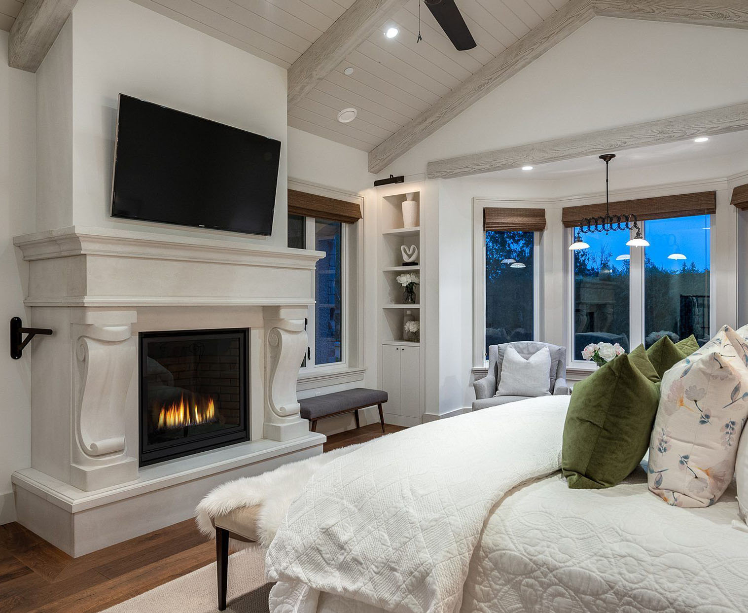 Master bedroom fireplace with a beautiful cast surround featuring scrolled legs, a hearth and mantle with wall mounted TV.