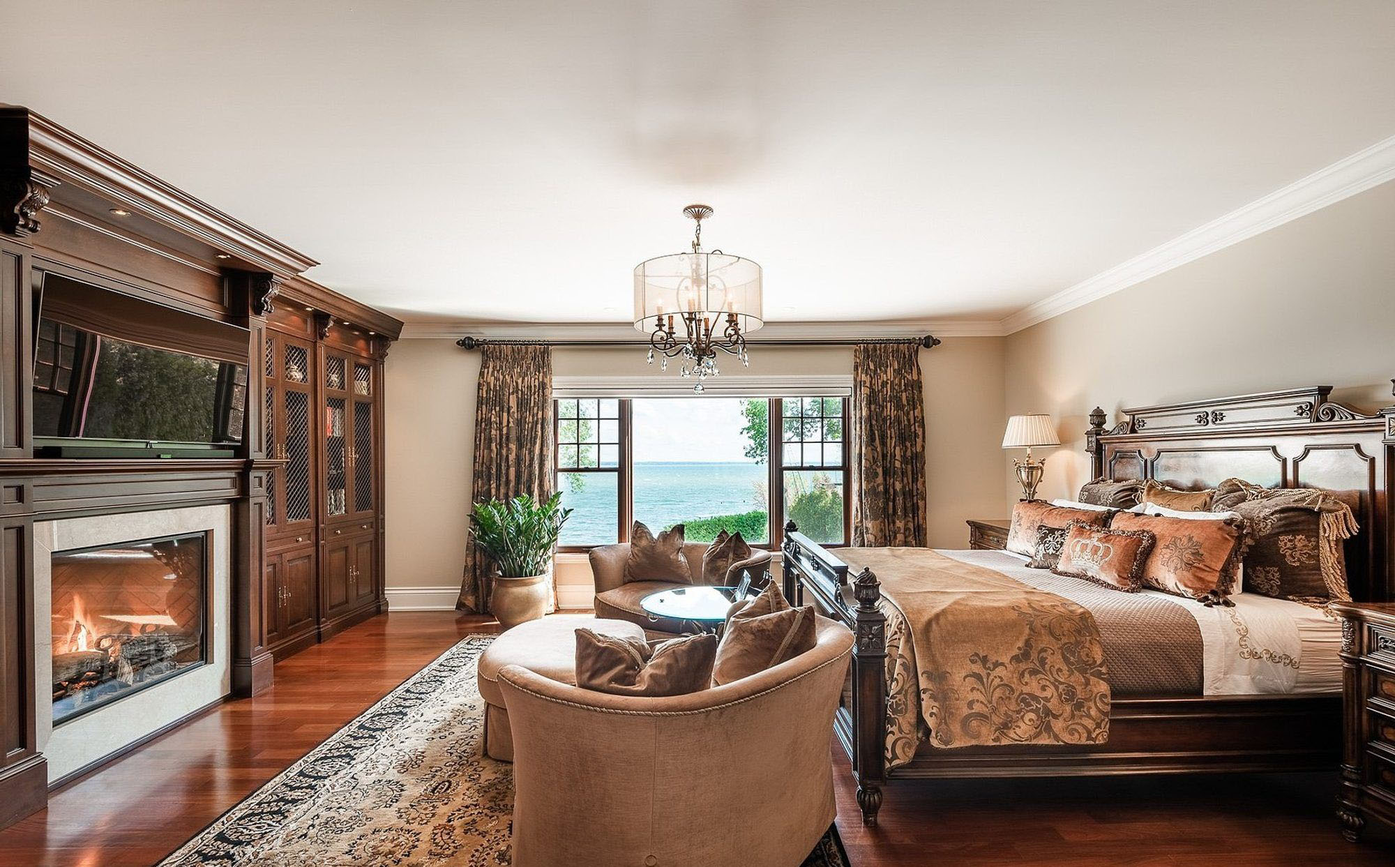 Beautiful master bedroom with a large gas burning fireplace and wood surround.