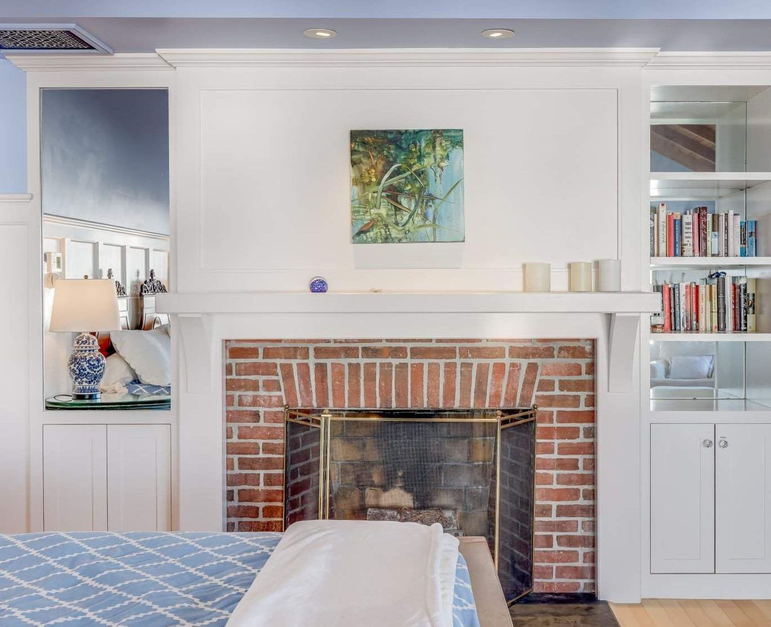 Classic red brick wood burning bedroom fireplace with a wood surround and built ins painted white.