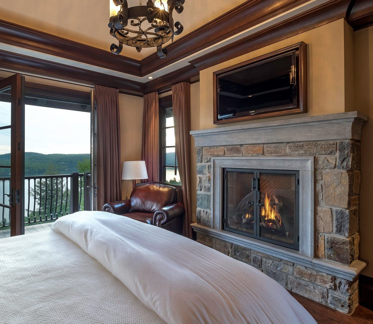 Country bedroom including a wood burning fireplace with real stone and cast cement trim. fireplace design ideas.
