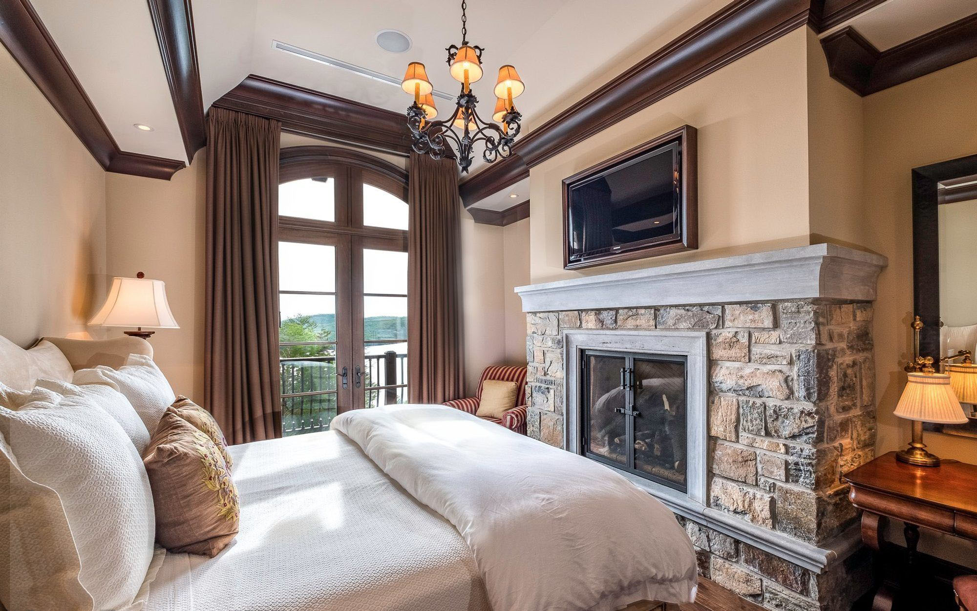Small country style bedroom with a warm color scheme and a stone bedroom fireplace. bedroom fireplace ideas.