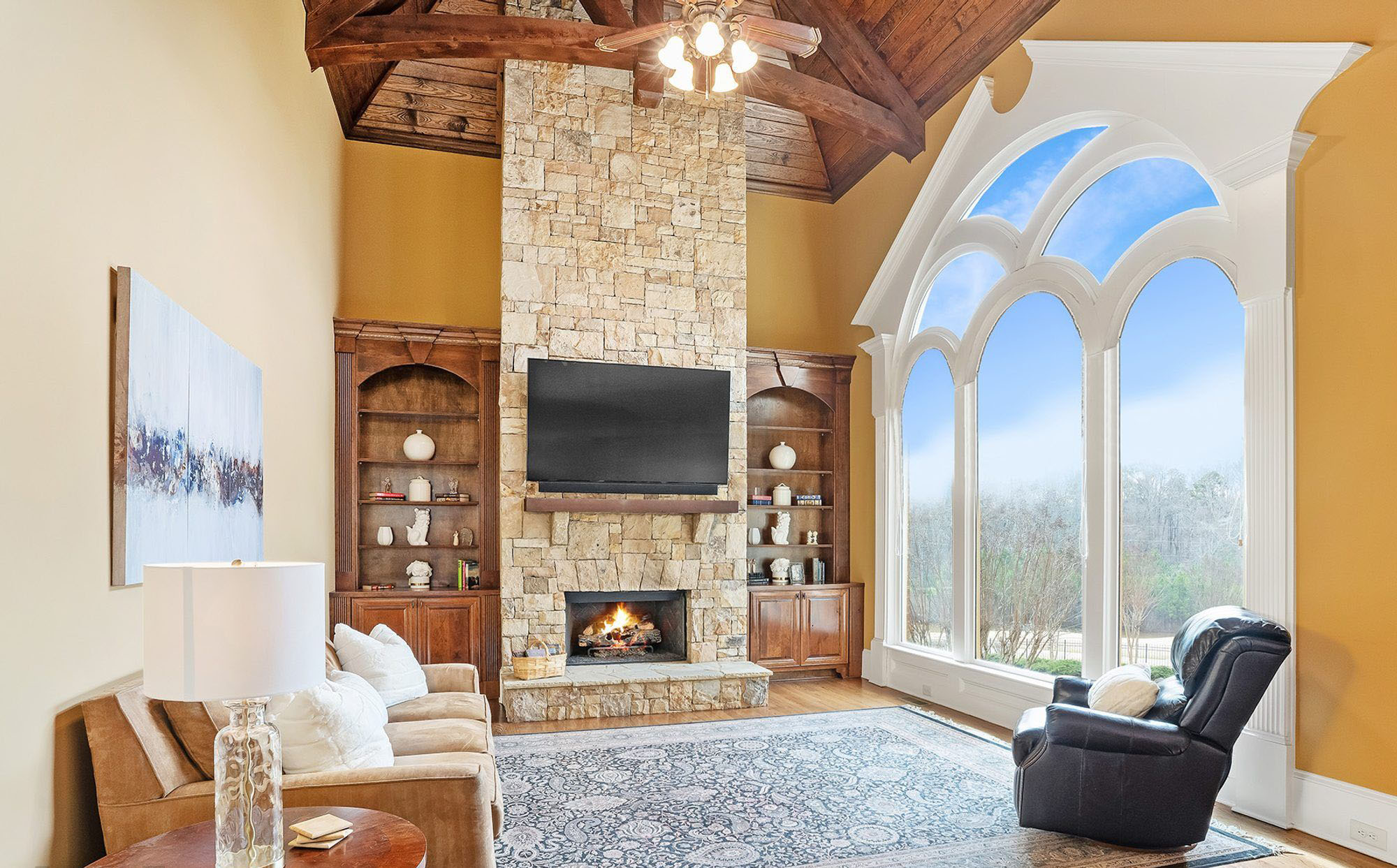 Wood burning fireplace with stacked stone veneer and a raised stone hearth. fireplace design ideas.