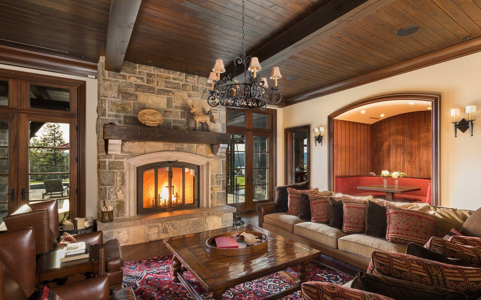 Beautiful living room with a rustic design featuring a real stone fireplace with raised hearth and wood shelf, rich wood trim and exposed ceiling beams.