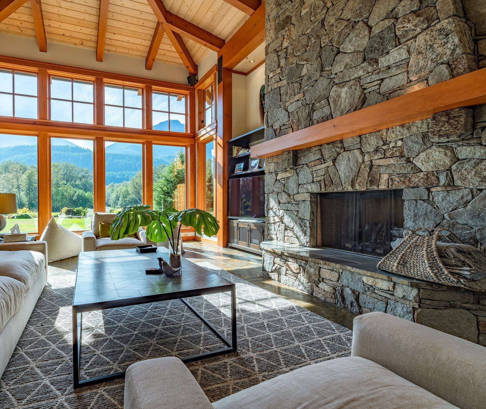 Slate gray stacked stone fireplace with a raised hearth and natural wood mantle.