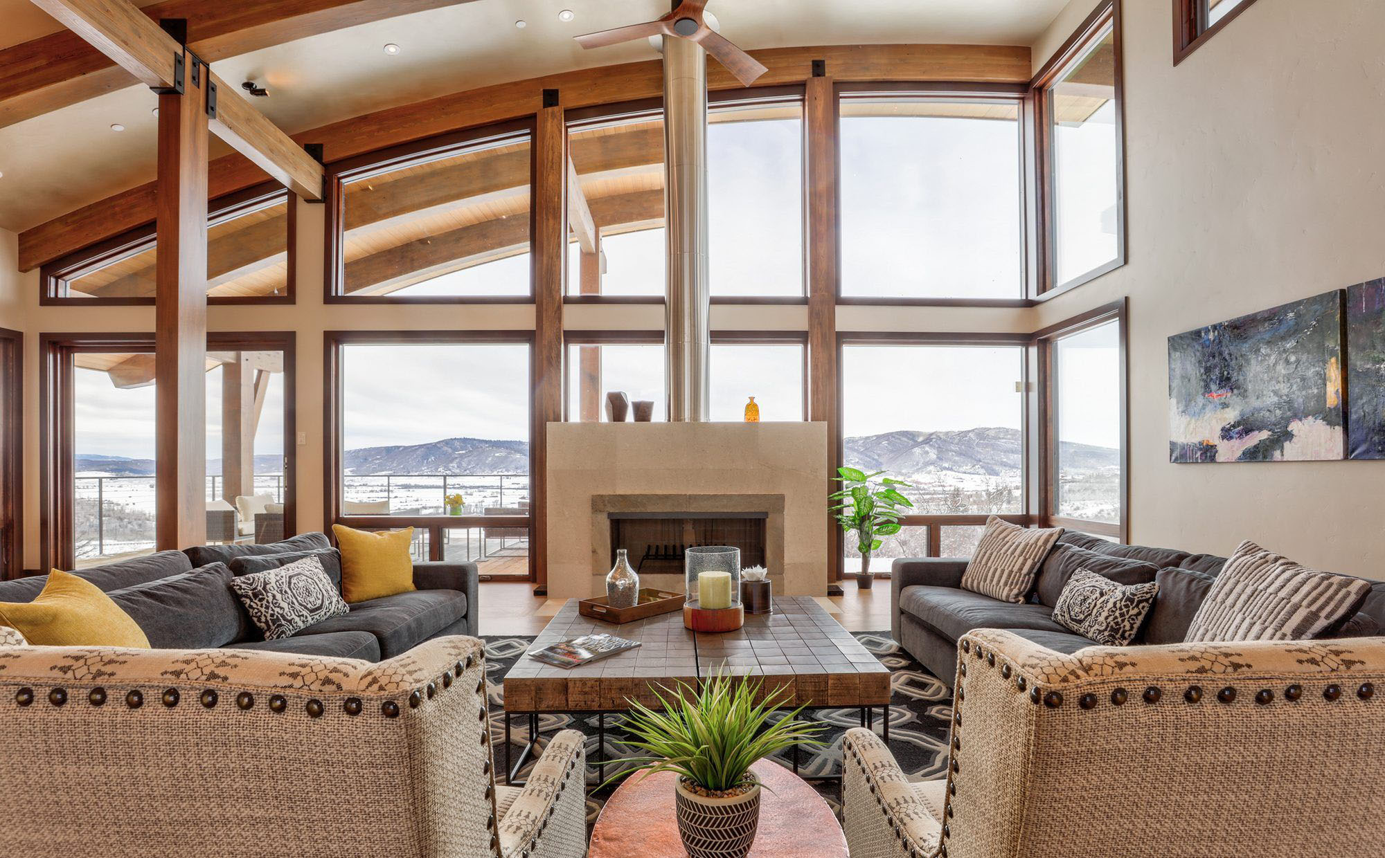 Standalone fireplace surround in front of a spectacular country view and a wall of glass.