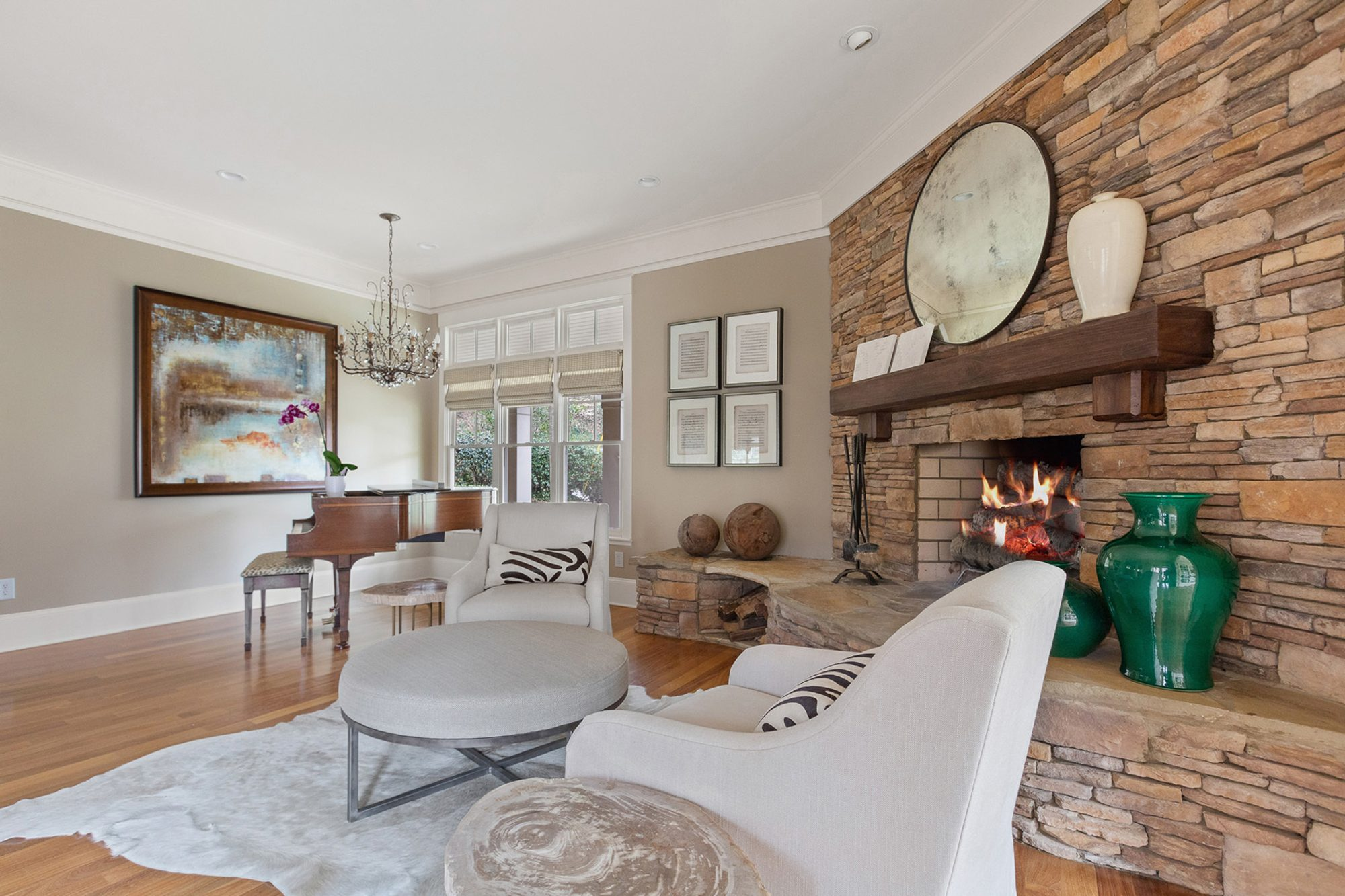 Fireplace surround built with warm colored stacked fieldstone, a large raised hearth and real wood shelf.