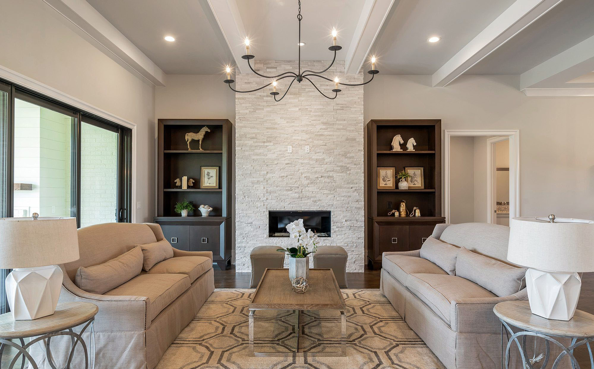 Warm cream colored ledge stone fireplace surround with a super clean design featuring no shelf or hearth. Floor to ceiling stone with a gas firebox. fireplace design ideas.